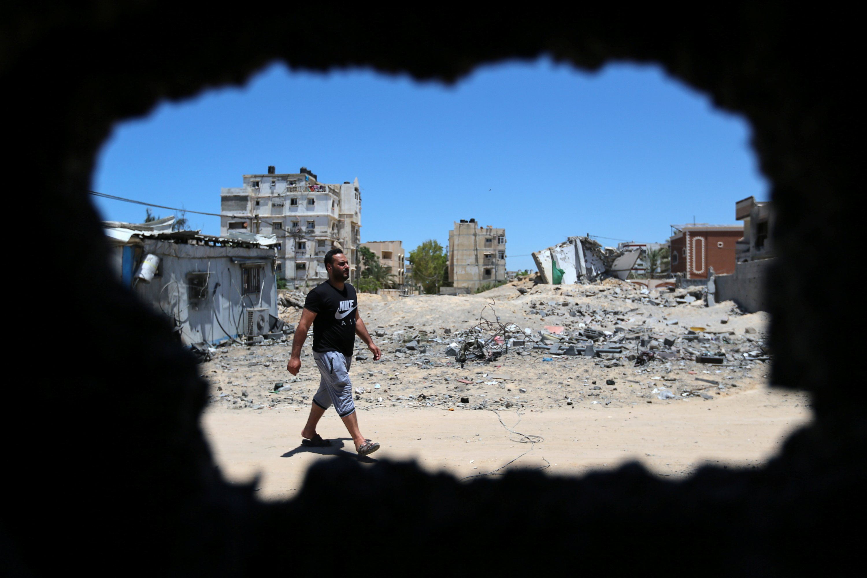 Ibrahim Dwedar, who evacuated Palestinian Omar Shahin's horses, which were wounded during the recent Israeli airstrikes, is seen through a damaged stable in the northern Gaza Strip, May 24, 2021. (Reuters Photo)