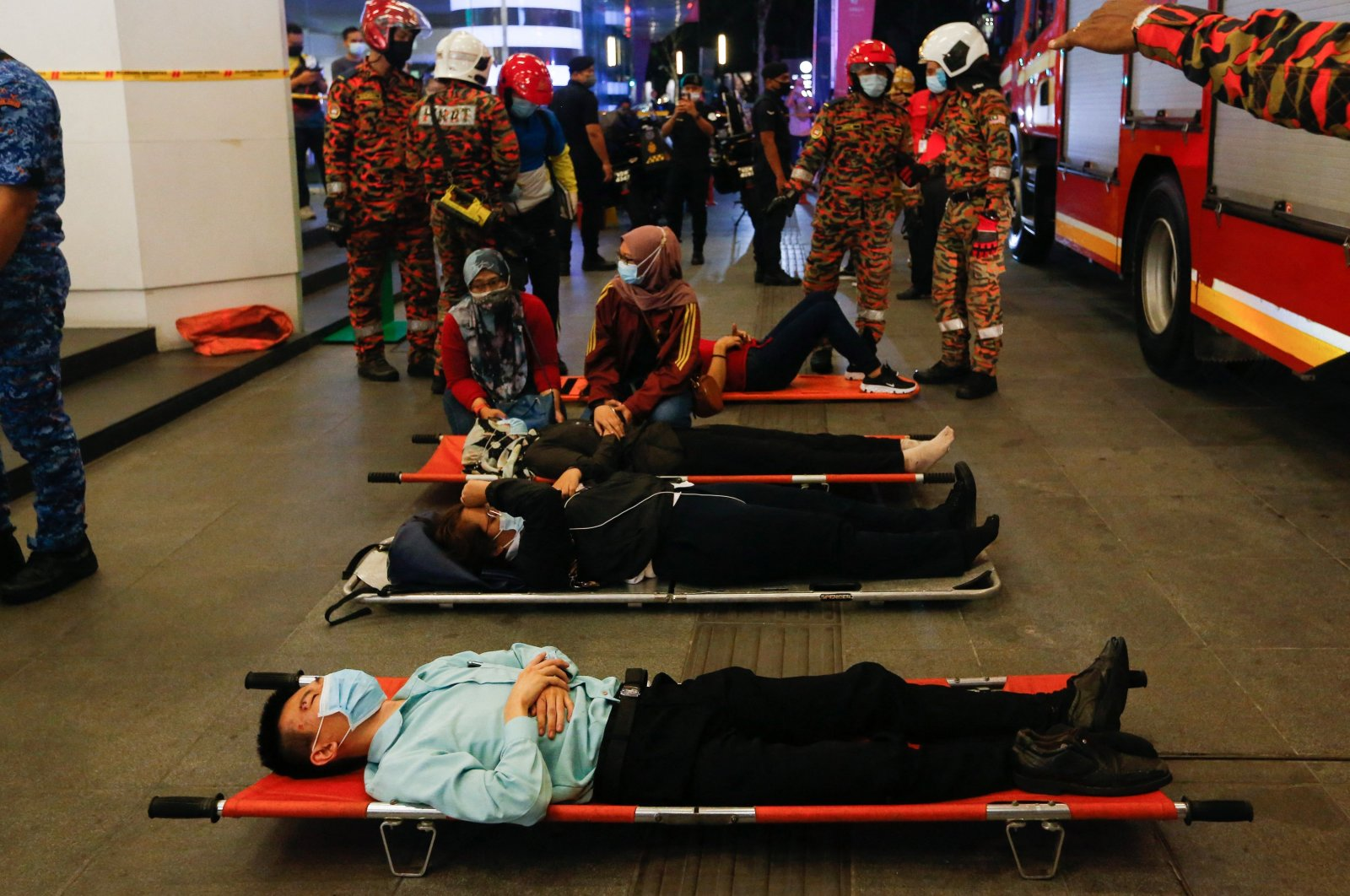 Injured passengers lie on stretchers outside KLCC station after an accident involving two Light-Rail Transit (LRT) trains in Kuala Lumpur, Malaysia, May 24, 2021. (AFP Photo)