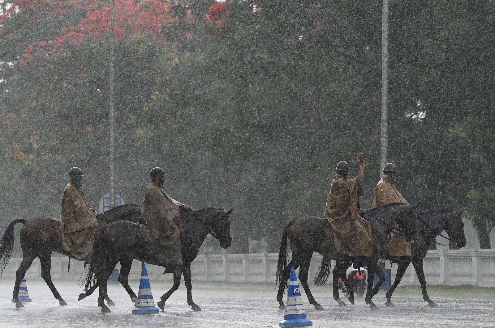 Mounted police ride on their horses along a road during rainfall in Kolkata, India, May 24, 2021. (AFP Photo)