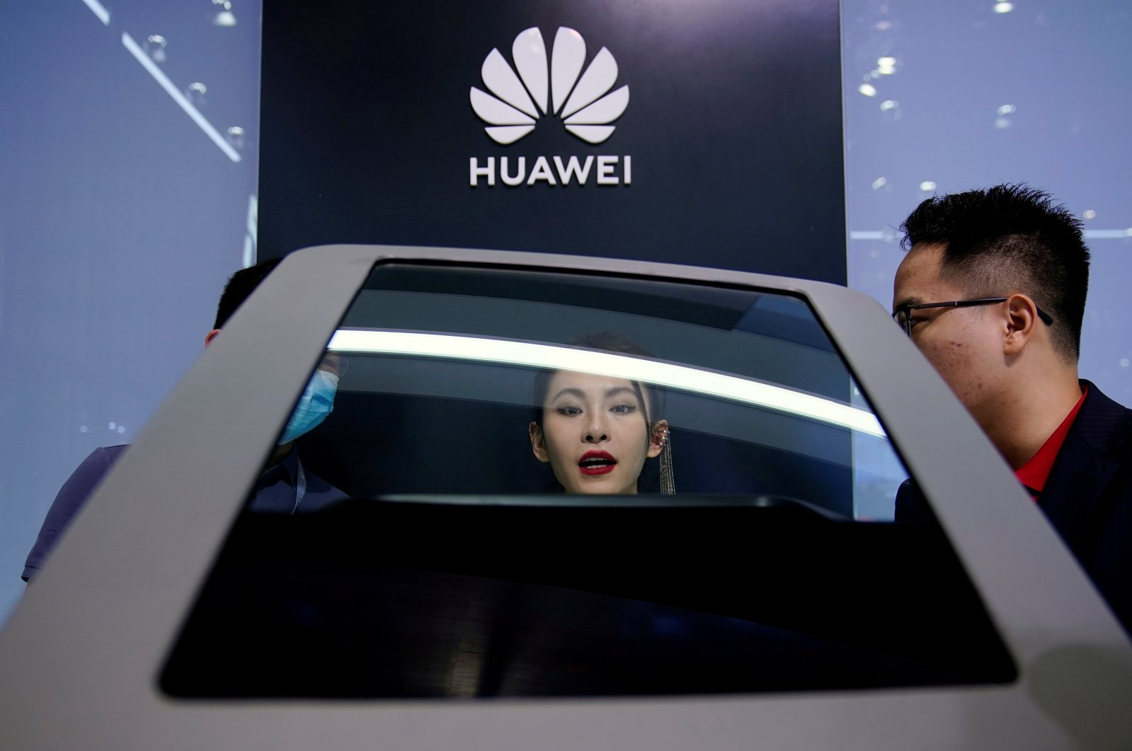 People look at a display near a Huawei logo during a media day for the Auto Shanghai show, Shanghai, China, April 19, 2021. (Reuters Photo)