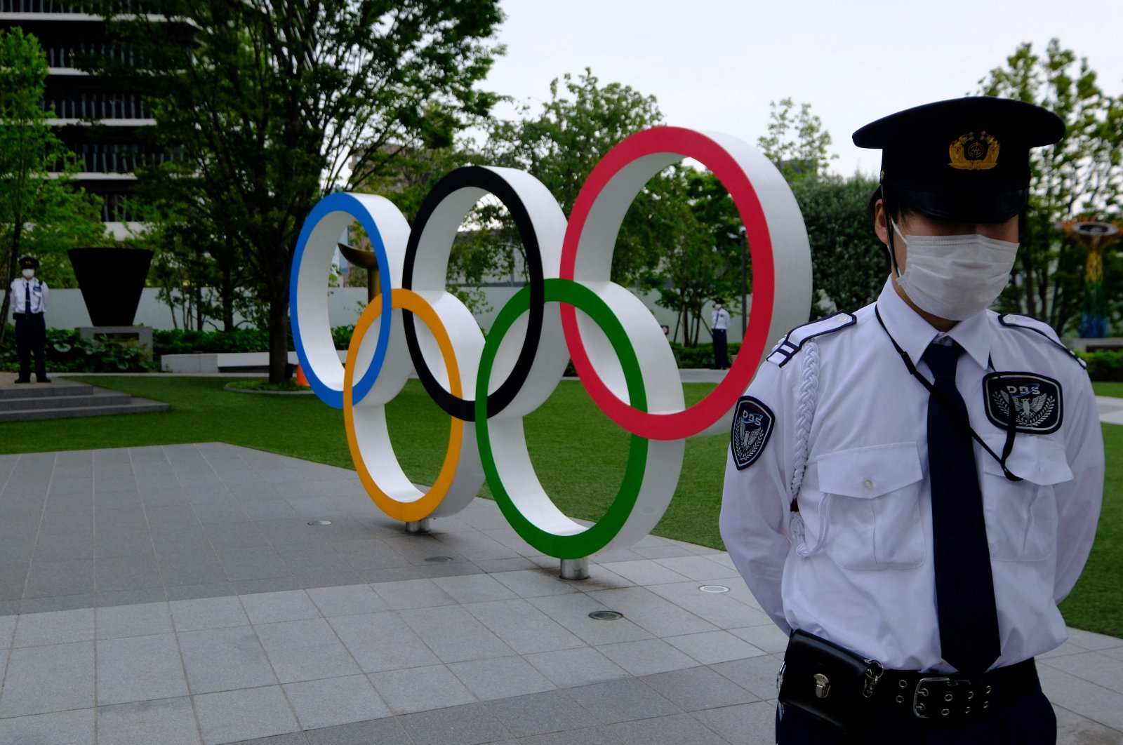Security guards keep watch next to the Olympic Rings while people take part in a protest against the hosting of the 2020 Tokyo Olympic Games, in front of the headquarters building of the Japanese Olympic Committee in Tokyo, Japan, May 18, 2021. (AFP Photo)