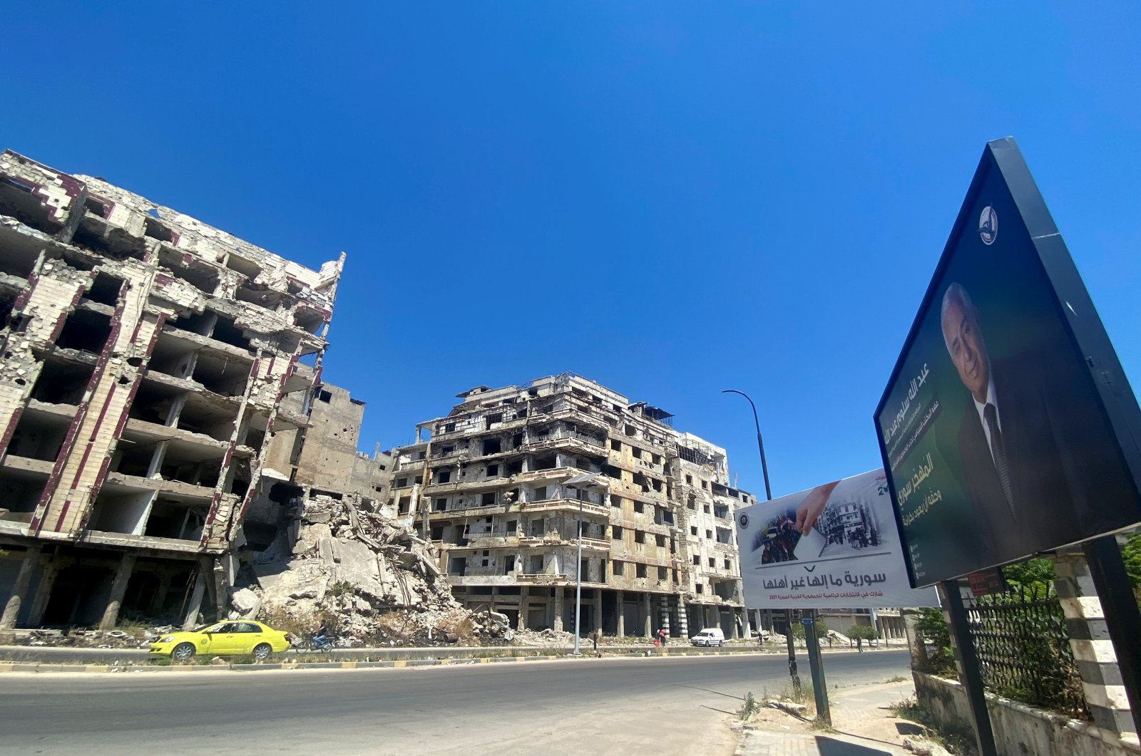 A view shows an election campaign billboard of presidential candidate Abdullah Salloum, near damaged buildings in Homs, Syria, May 23, 2021. (REUTERS)