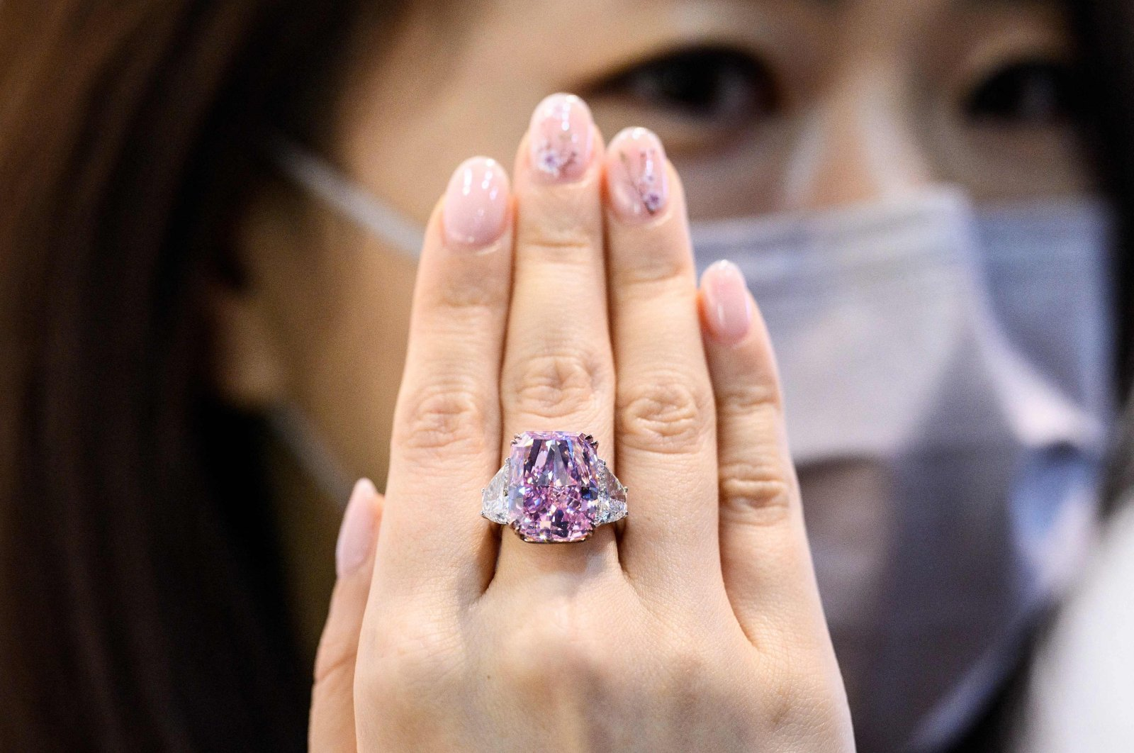 A woman displays the Sakura Diamond, a 15.81 carat fancy vivid purple-pink diamond ring, during a Christies pre-auction preview in Hong Kong, May 20, 2021. (AFP Photo)