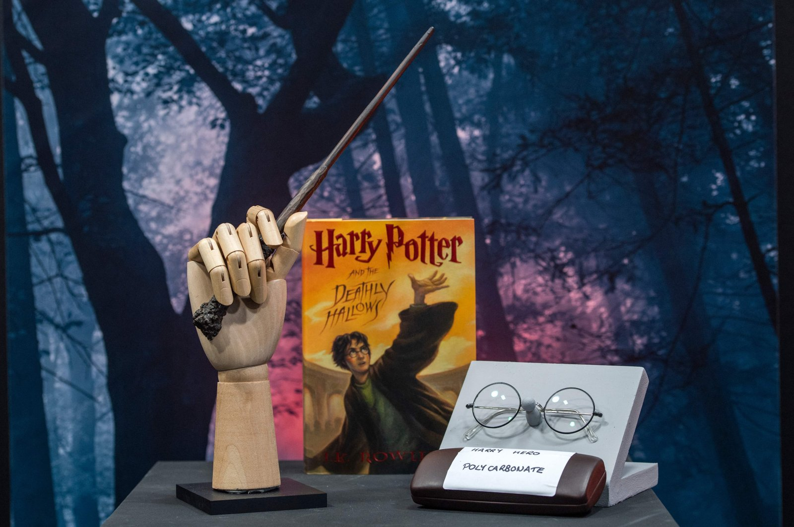"""Harry Potter's wand and eyeglasses are displayed next to a copy of """"Harry Potter and the Deathly Hallows"""" during a press preview of Prop Store's Iconic Film & TV Memorabilia in Valencia, California, May 14, 2021. (AFP Photo)"""