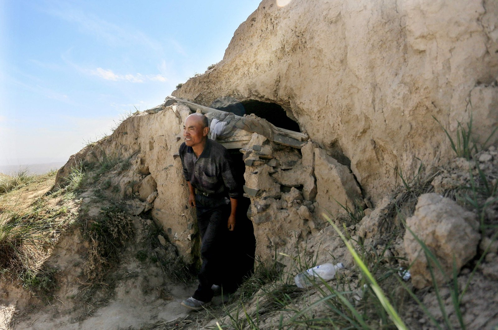 Shepherd Zhu Keming, hailed as a hero in China for rescuing six ultramarathon runners when extreme weather hit the area leaving at least 21 dead, shows the cave-dwelling where he sheltered the stricken athletes near the city of Baiyin, in China's northwestern Gansu province, May 24, 2021. (AFP Photo)