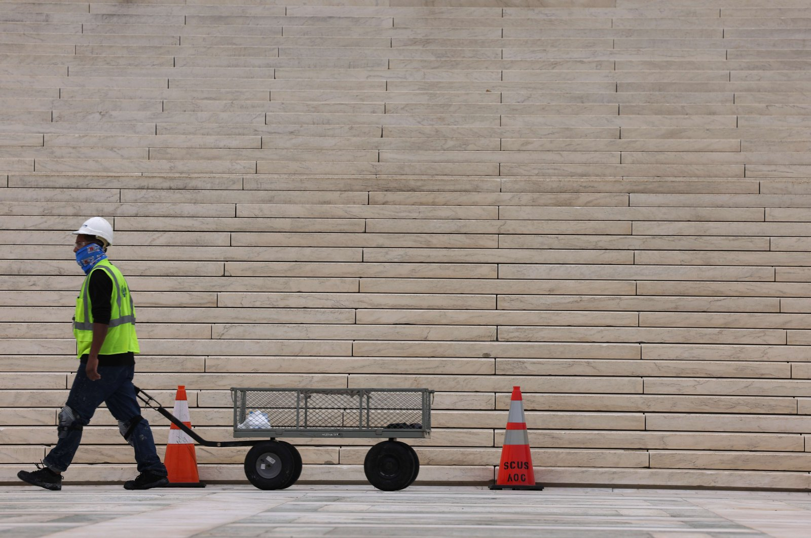 A worker walks past cones set up in front of the U.S. Supreme Court building, Washington, D.C., U.S. May 24, 2021. (AFP Photo)