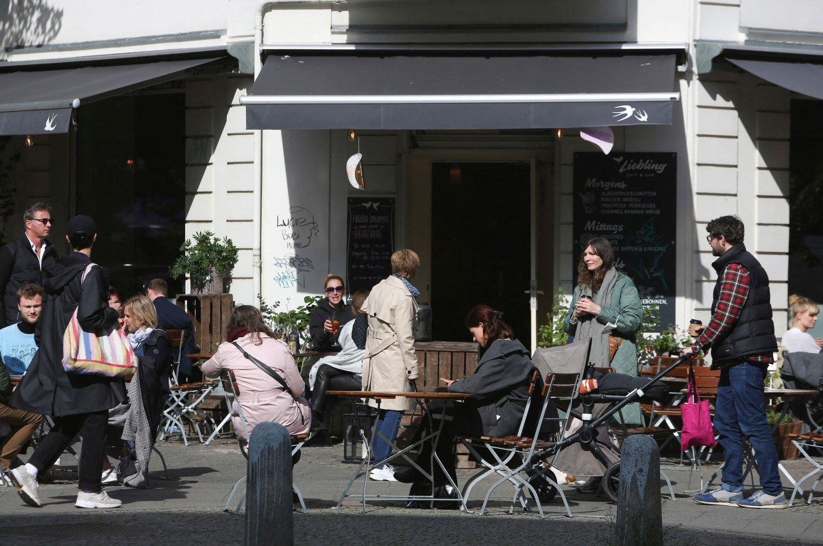 Guests sit outside a cafe after businesses were allowed to reopen outdoor seating amid the ongoing COVID-19 pandemic, in Berlin, Germany, May 22, 2021. (AFP Photo)