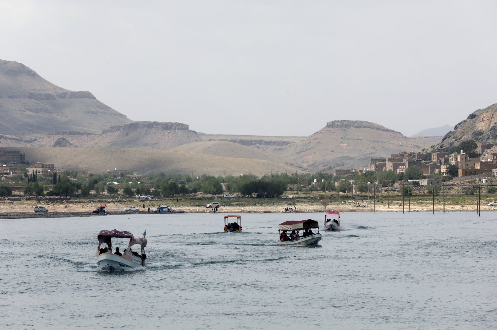 People ride boats during an excursion at a dam in Sayyan near Sanaa, Yemen, May 16, 2021. (Reuters Photo)