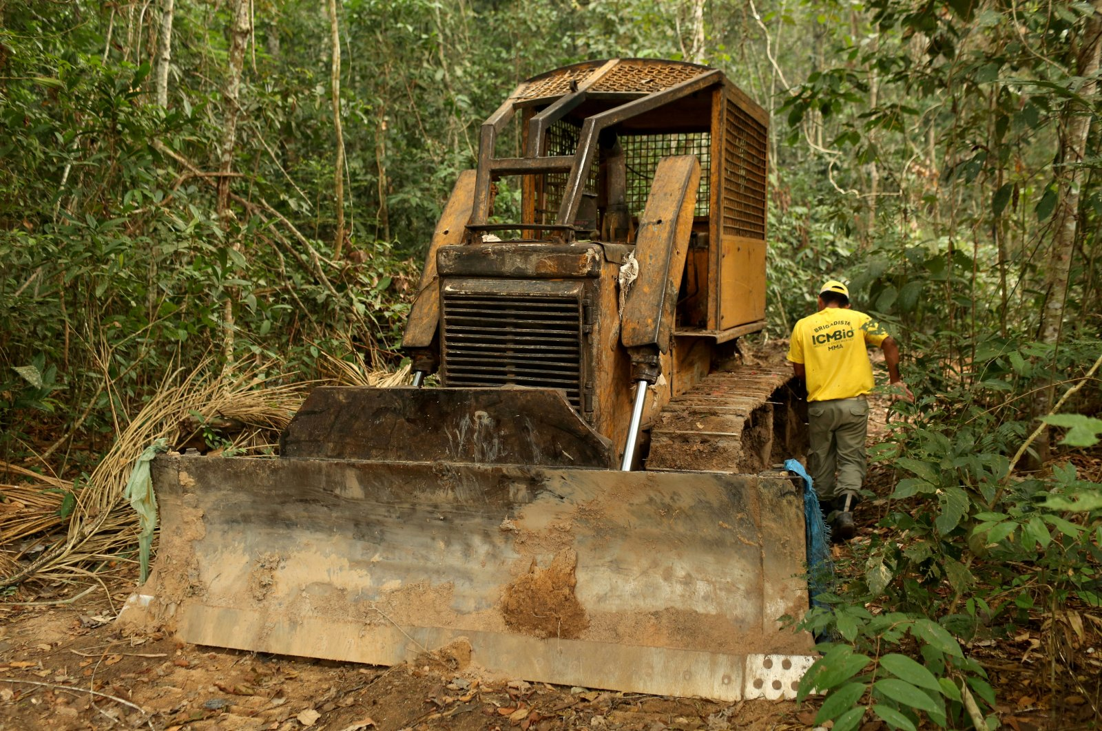 A member of the Chico Mendes Institute for Biodiversity Conservation (ICMBio) walks next a tractor used for deforestation at the National Forest Bom Futuro in Rio Pardo, Rondonia State, Brazil, Sept. 13, 2019. (Reuters Photo)