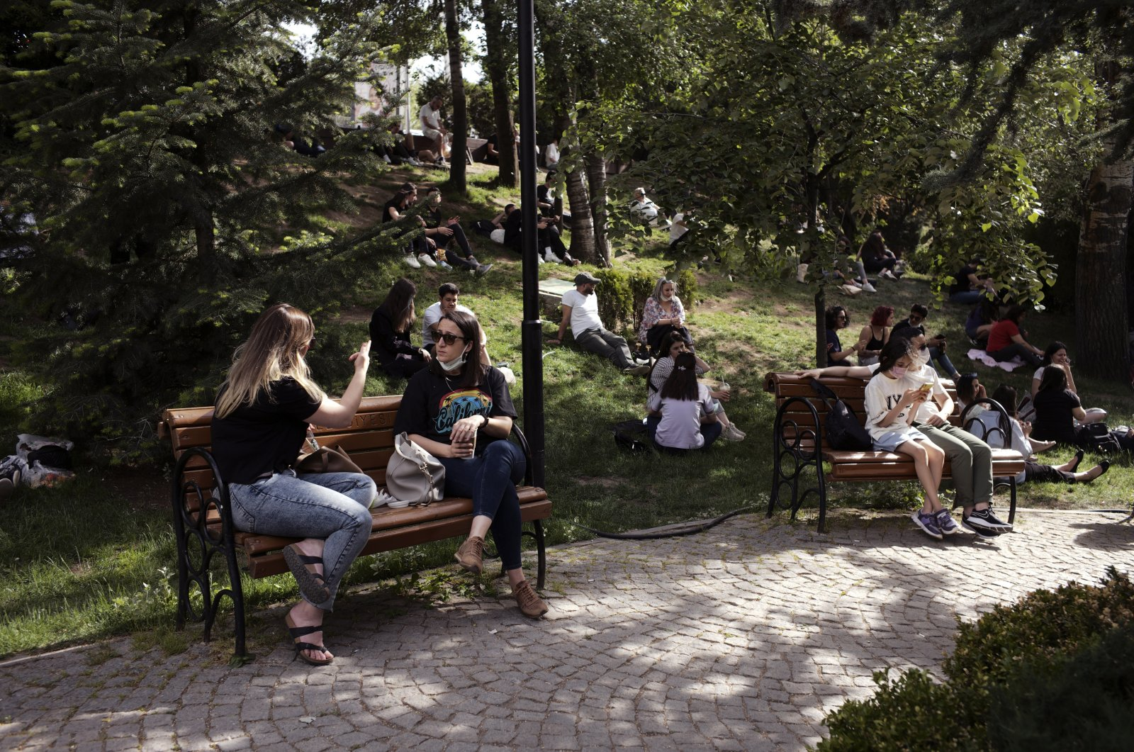 People crowd a public garden hours before a weekend curfew, in Ankara, Turkey, Friday, May 21, 2021. (AP Photo)