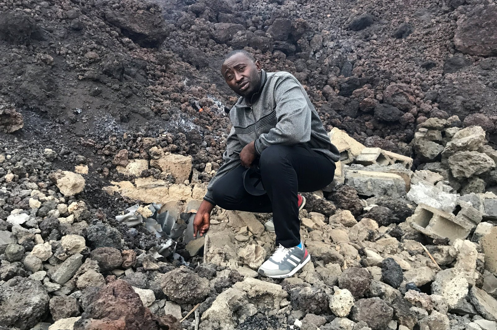 Nzanzu Muhiwa Zawadi, 37, points to the location of his house, which is covered by lava after the eruption of Mount Nyiragongo volcano, near Goma, in the Democratic Republic of Congo, May 24, 2021. (Reuters Photo)
