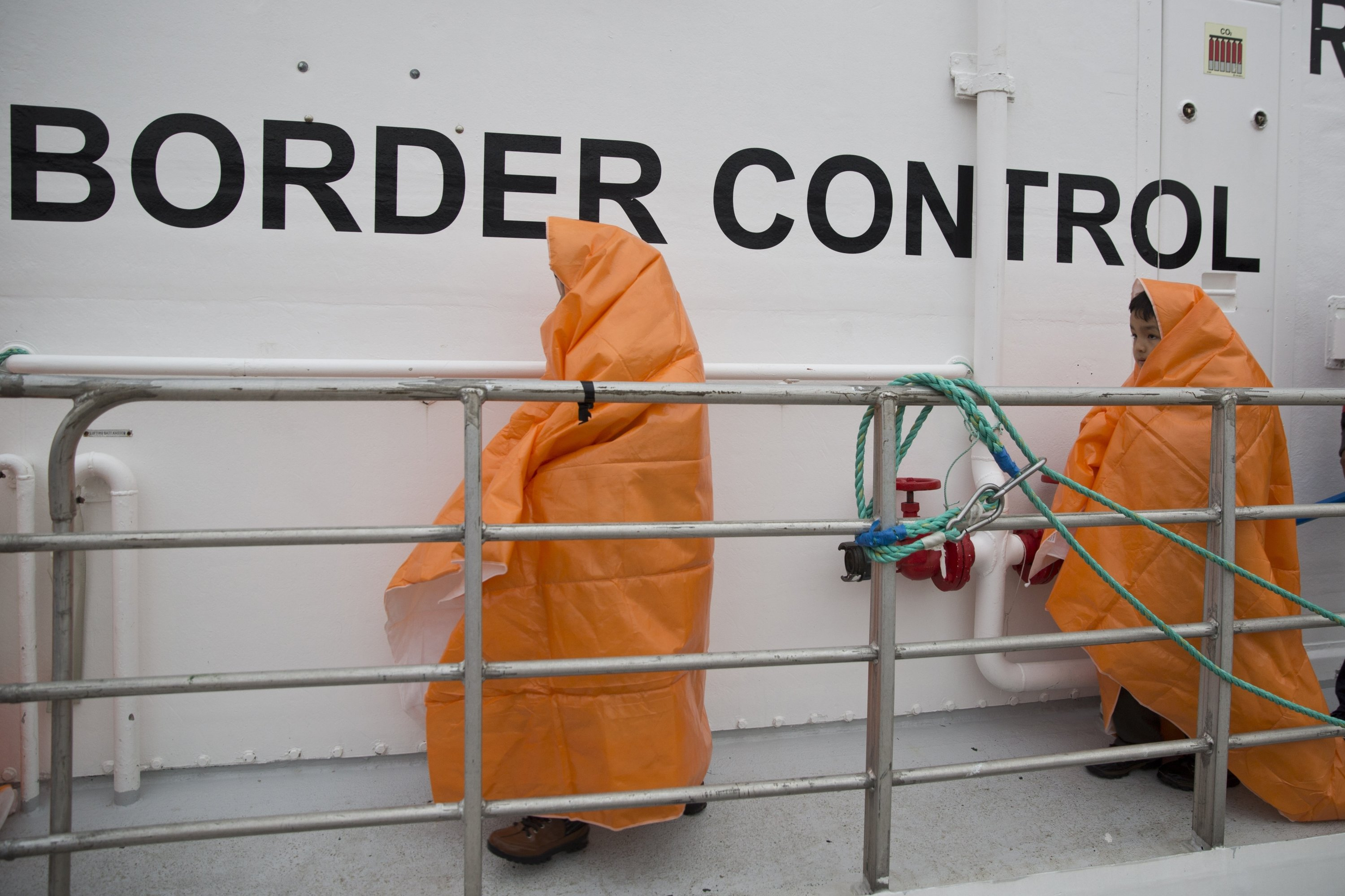 Two children prepare to disembark with other 53 migrants and refugees from a Norwegian Frontex patrol vessel after they were rescued near the shores of the island of Lesbos, Greece, March 22, 2016. (AP Photo)