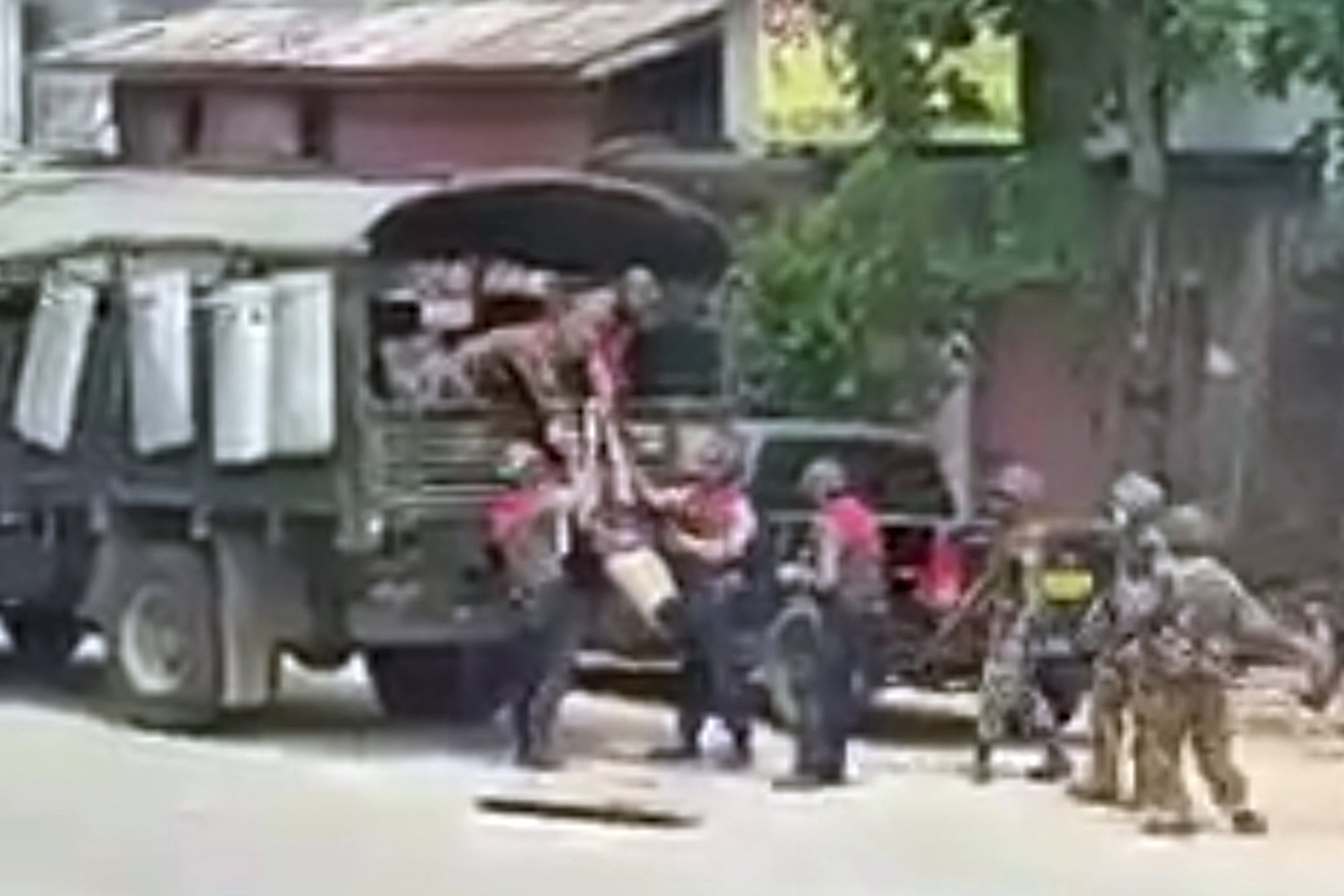 In this March 26, 2021 image from video obtained by The Associated Press, security forces pull the body of an unidentified individual into a military truck in Myeik, Myanmar. (AP Photo)
