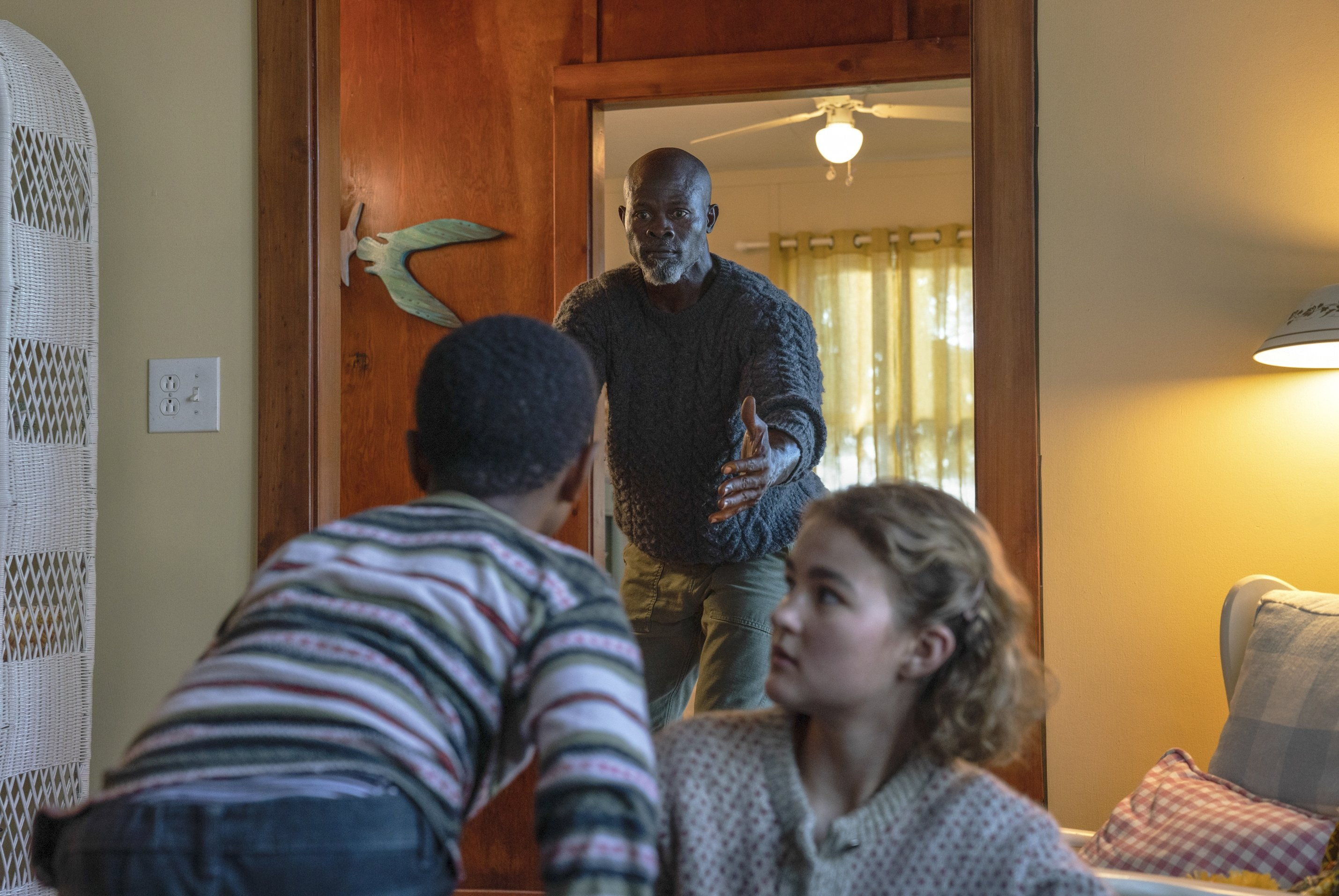 Actor Djimon Hounsou, in the background, calls a kid towards him who is sitting with Millicent Simmonds, in a scene from 'A Quiet Place Part II.' (Paramount Pictures via AP)