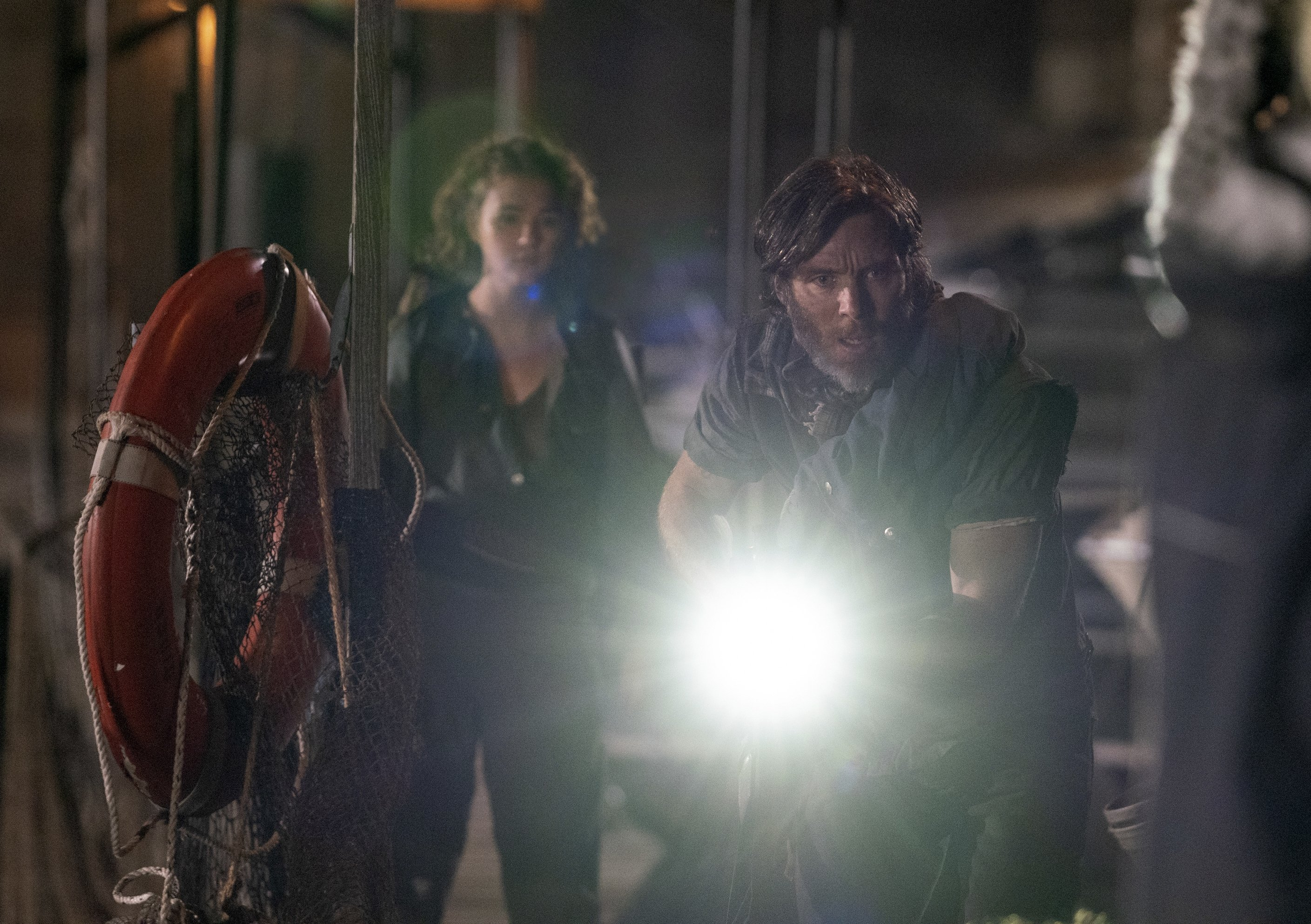 Millicent Simmonds (L) and Cillian Murphy (R) who is holding a flaslight attached to weapon, walk through an abandoned location,in a scene from'A Quiet Place Part II.' (Paramount Pictures via AP)