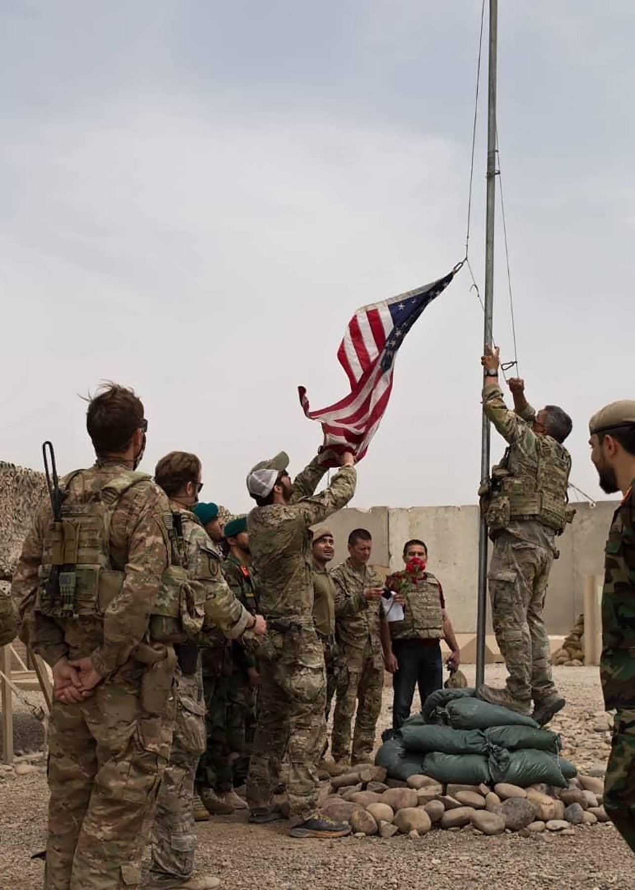 A U.S. flag is lowered as American and Afghan soldiers attend a handover ceremony from the U.S. Army to the Afghan National Army, at Camp Anthonic, in Helmand province, southern Afghanistan, May 2, 2021. (AP Photo)
