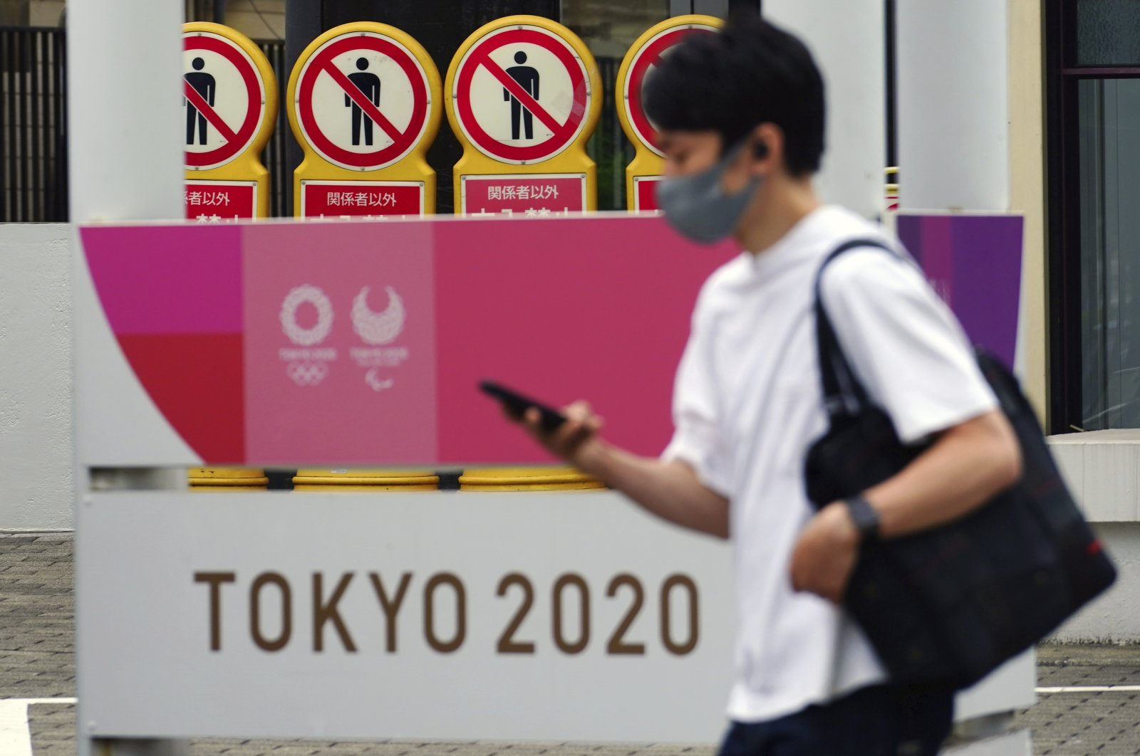 A man in a protective mask against the coronavirus walks past a Tokyo 2020 Olympic and Paralympic Games banner, Tokyo, Japan, May 11, 2021. (AP Photo)