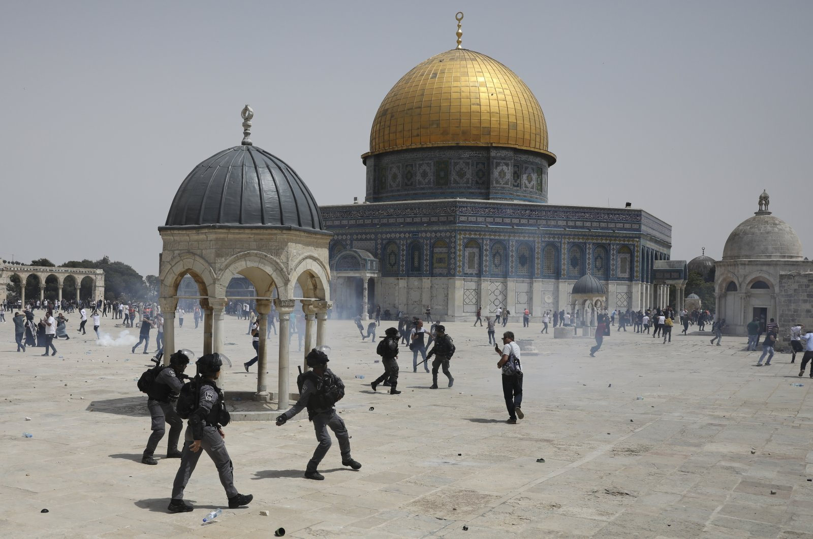Palestinians run from stun grenades thrown by Israeli police in front of the Dome of the Rock in the Al-Aqsa compound, East Jerusalem, occupied Palestine, May 21, 2021. (AP Photo)