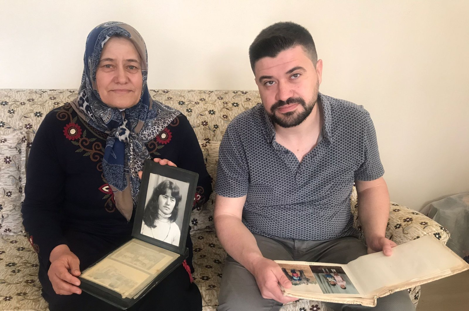Hatice Özdemir (L) and her son Mümin, who were forced to leave Bulgaria in 1989, show their family album in their home, in Kocaeli, northwestern Turkey, May 21, 2021. (AA PHOTO)