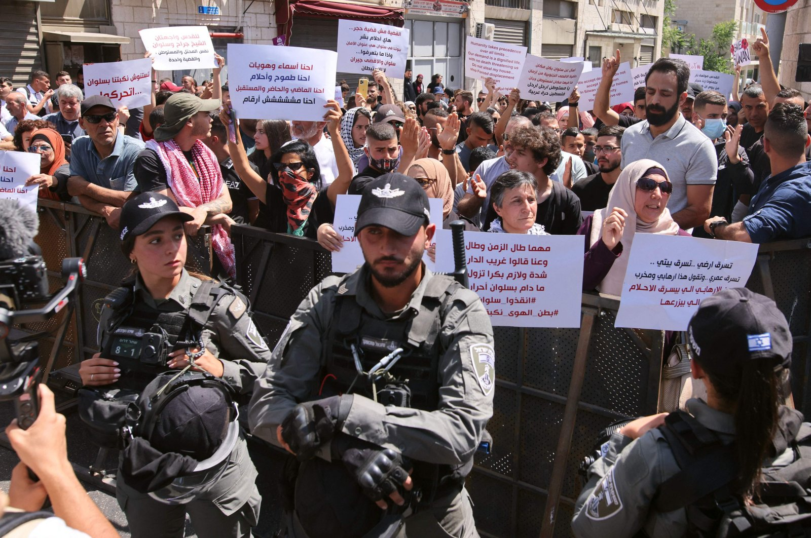 Israeli security forces keep watch as Palestinians shout slogans outside a court during a protest over Israel's planned evictions of Palestinian families from homes in the eastern sector's Silwan district, in Jerusalem, May 26, 2021. (AFP Photo)