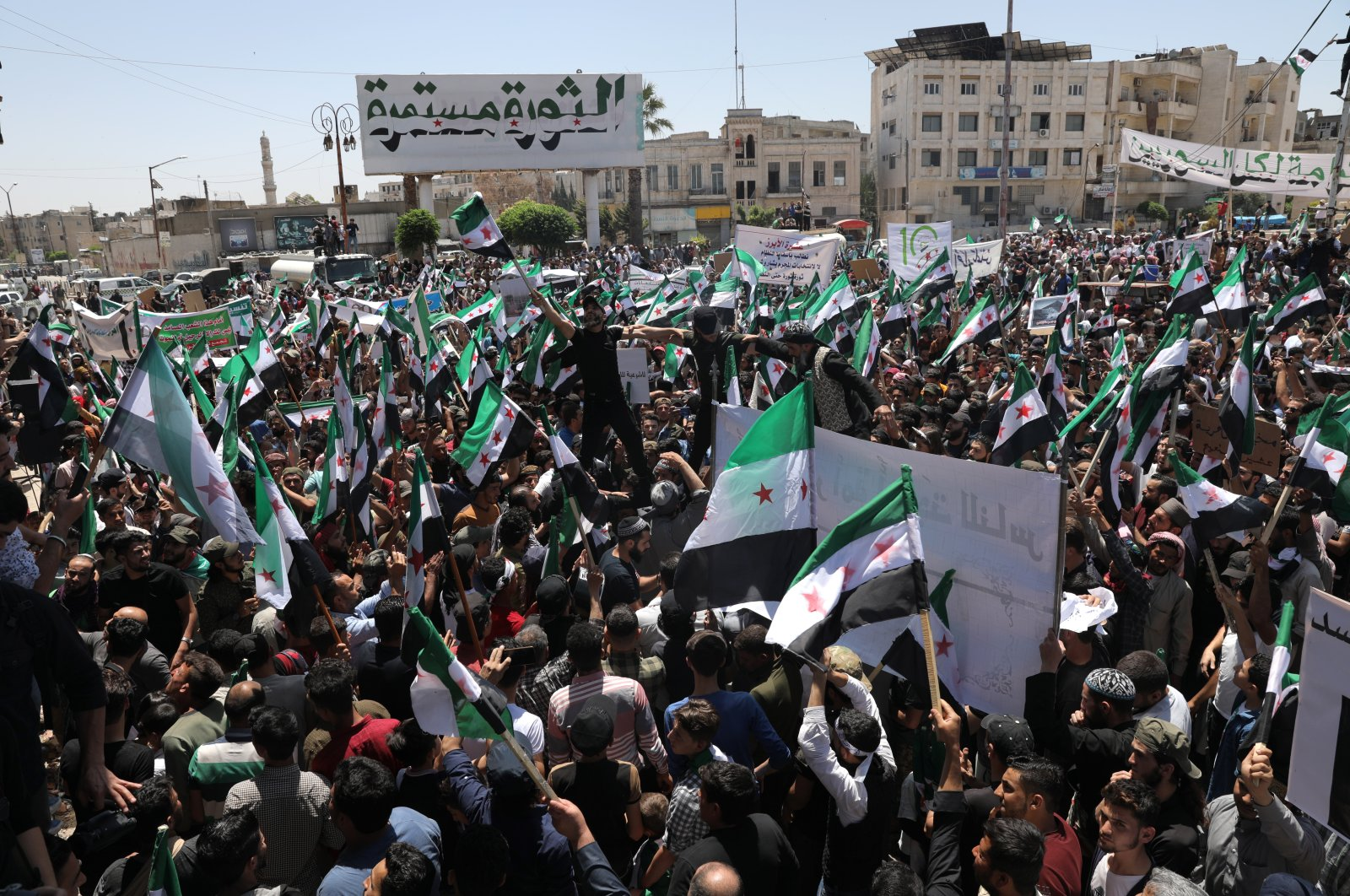 Syrian people hold placards during a protest against the presidential elections, in Idlib, Syria, May 26, 2021. (EPA Photo)