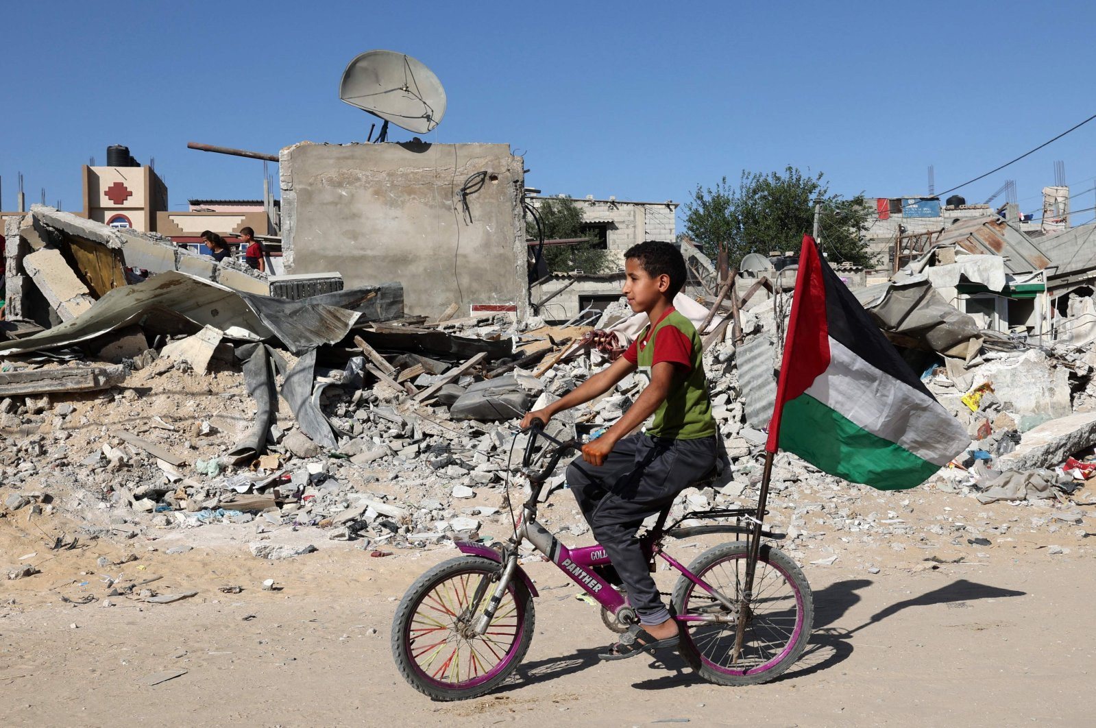 A Palestinian child rides his bicycle in front of the ruins of a building destroyed during recent Israeli bombing in Rafah, in the southern Gaza Strip, Palestine, on May 26, 2021. (AFP Photo)