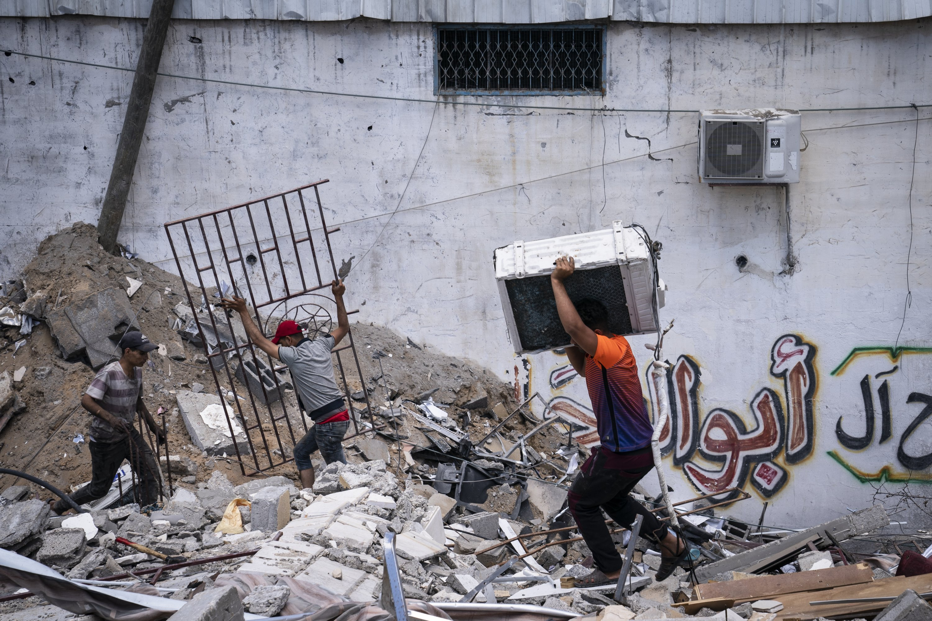 People reclaim valuable materials from a pile of debris of a building destroyed by an Israeli airstrike, in Gaza City, Palestine, May 22, 2021. (AP Photo)