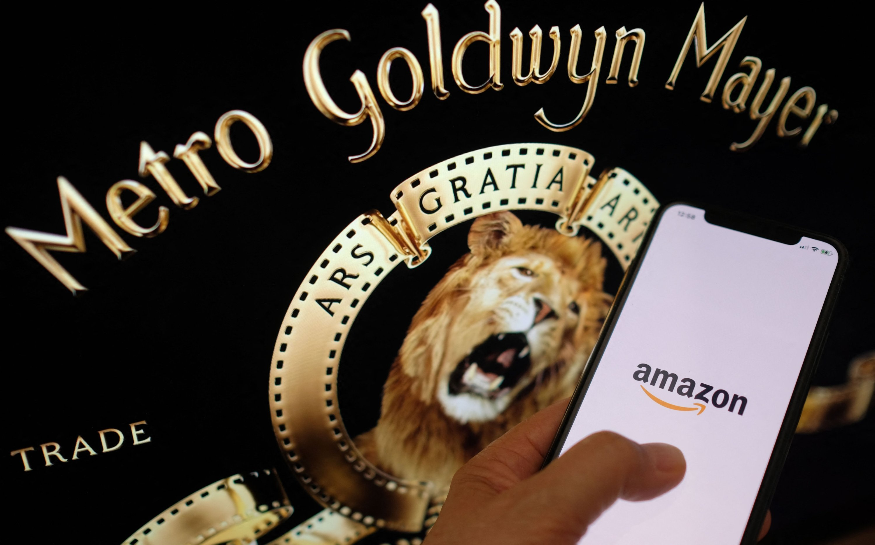 This illustration photo taken May 26, 2021, shows the Amazon logo on a smartphone in front of the MGM lion on a computer screen in Los Angeles. (AFP Photo)