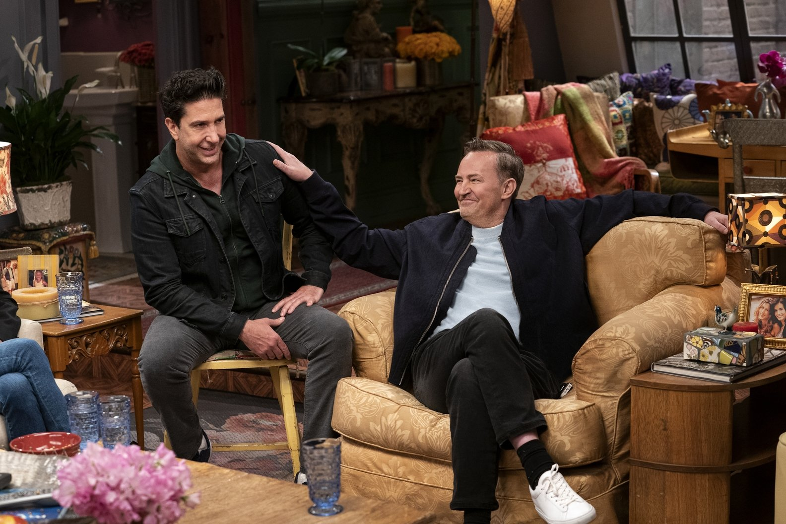 Matthew Perry (R) patsDavid Schwimmer on the shoulder as he sits down in the famous apartmentfrom the television series 'Friends' during the reunion special. (HBO Max via AP)