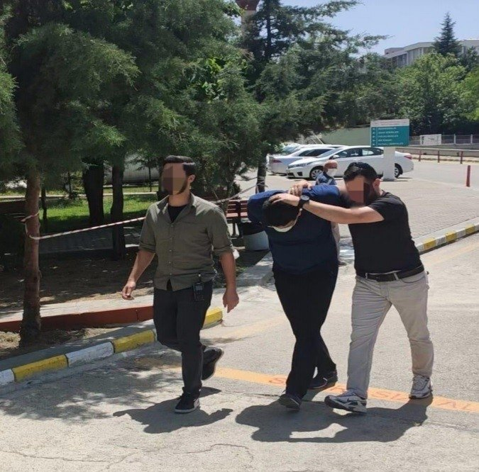 Police officers escort the captured suspect, in the capital Ankara, Turkey, May 27, 2021. (IHA PHOTO)