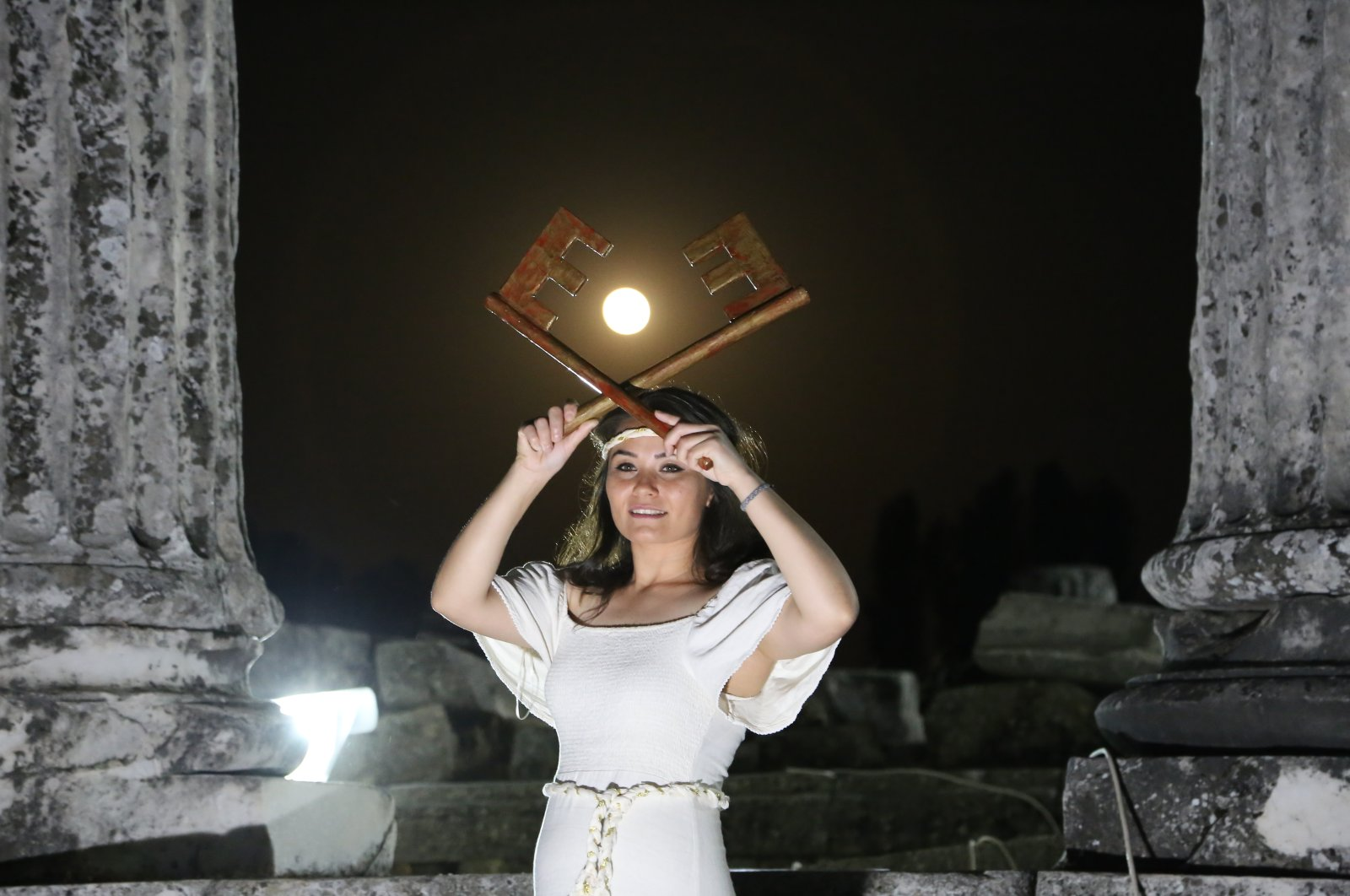 The actress portraying the goddess Hecate hold keys in front of the super moon at the Sanctuary of Hecate in Lagina, Muğla, southwestern Turkey, May 27, 2021. (AA Photo)