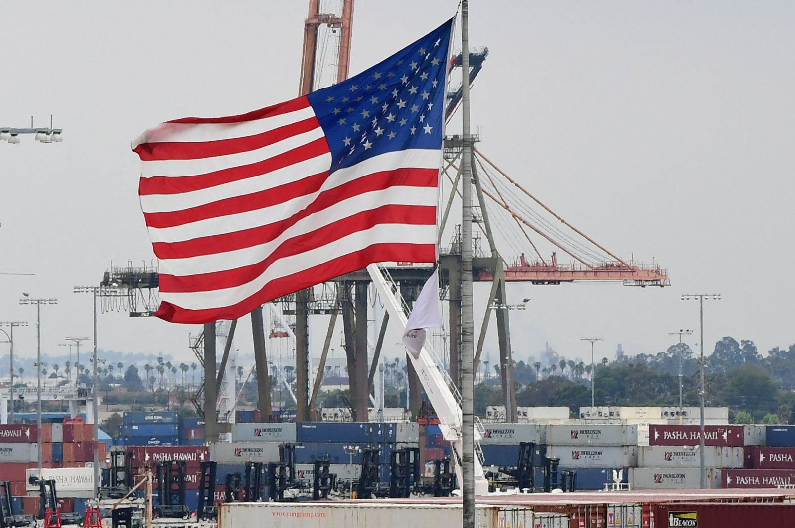 U.S. flag flies in the foreground as containers are seen at the Port of Los Angeles, San Pedro, California, the U.S., June 18, 2019. (AFP Photo)
