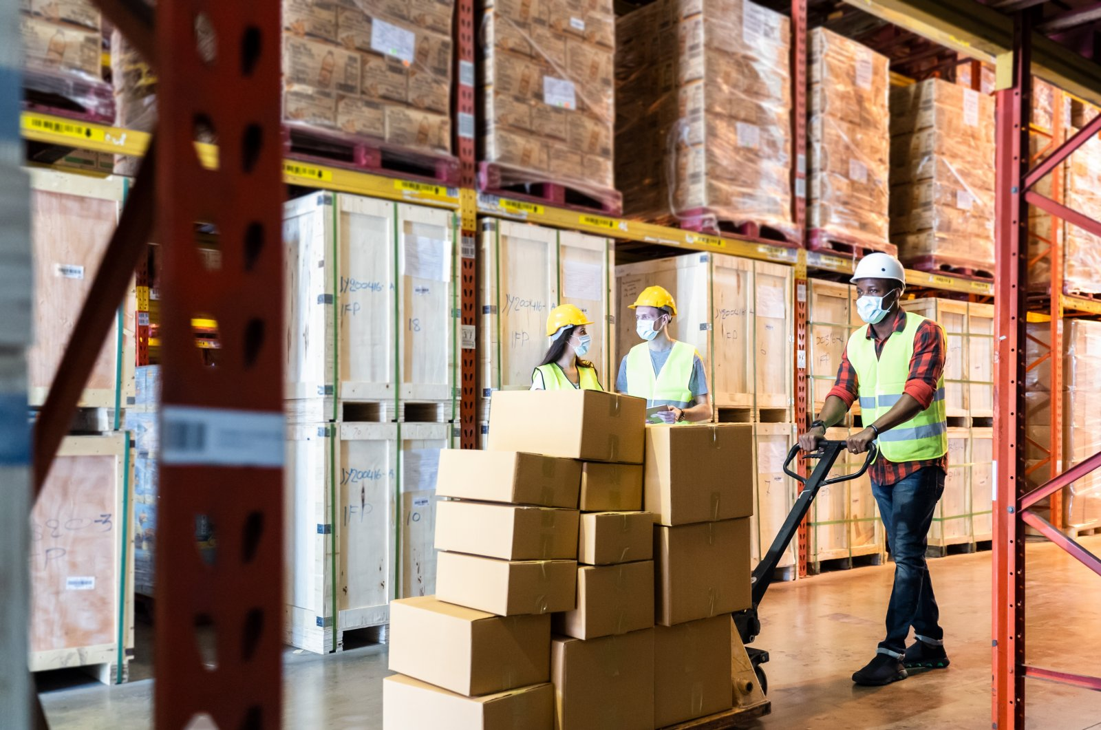Postal workers in protective masks against the coronavirus work in a warehouse. (Photo by Shutterstock)