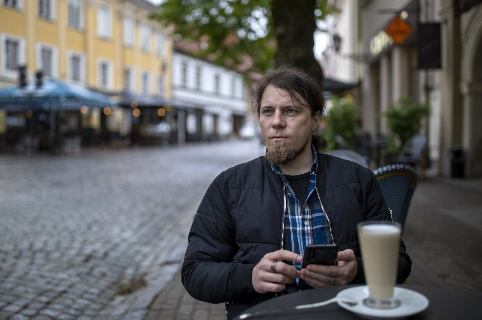 Viachka Krasulin, who fled Belarus after police arrested and beat him during demonstrations against authoritarian President Alexander Lukashenko in August 2020, sits at a cafe in Vilnius, Lithuania, May 19, 2021. (AP Photo)