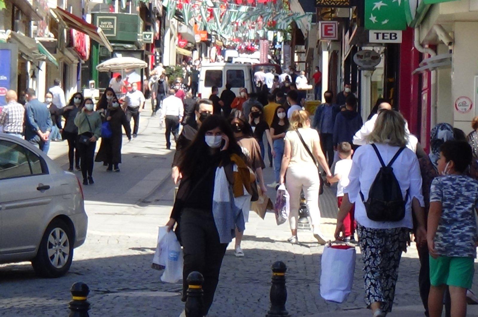 People wearing protective masks walk on a street in Giresun, northern Turkey, May 26, 2021. (İHA PHOTO)
