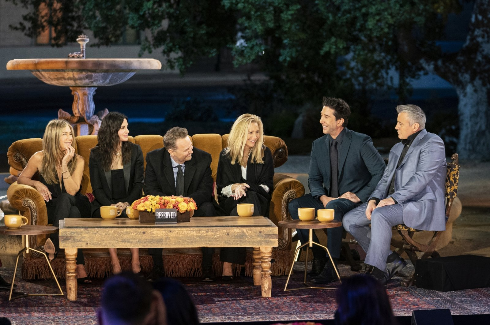 """From the left Jennifer Aniston, Courteney Cox, Matthew Perry, Lisa Kudrow, David Schwimmer and Matt LeBlanc sit around the famous sofa from the television series """"Friends"""" during the reunion special, with the water fountain from the show's intro in the background. (HBO Max via AP)"""