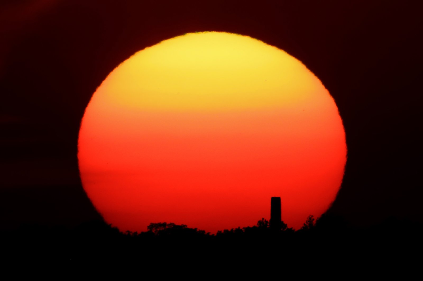 The sun sets behind a smokestack in the distance in Kansas City, Missouri, U.S., June 26, 2020. (AP Photo)