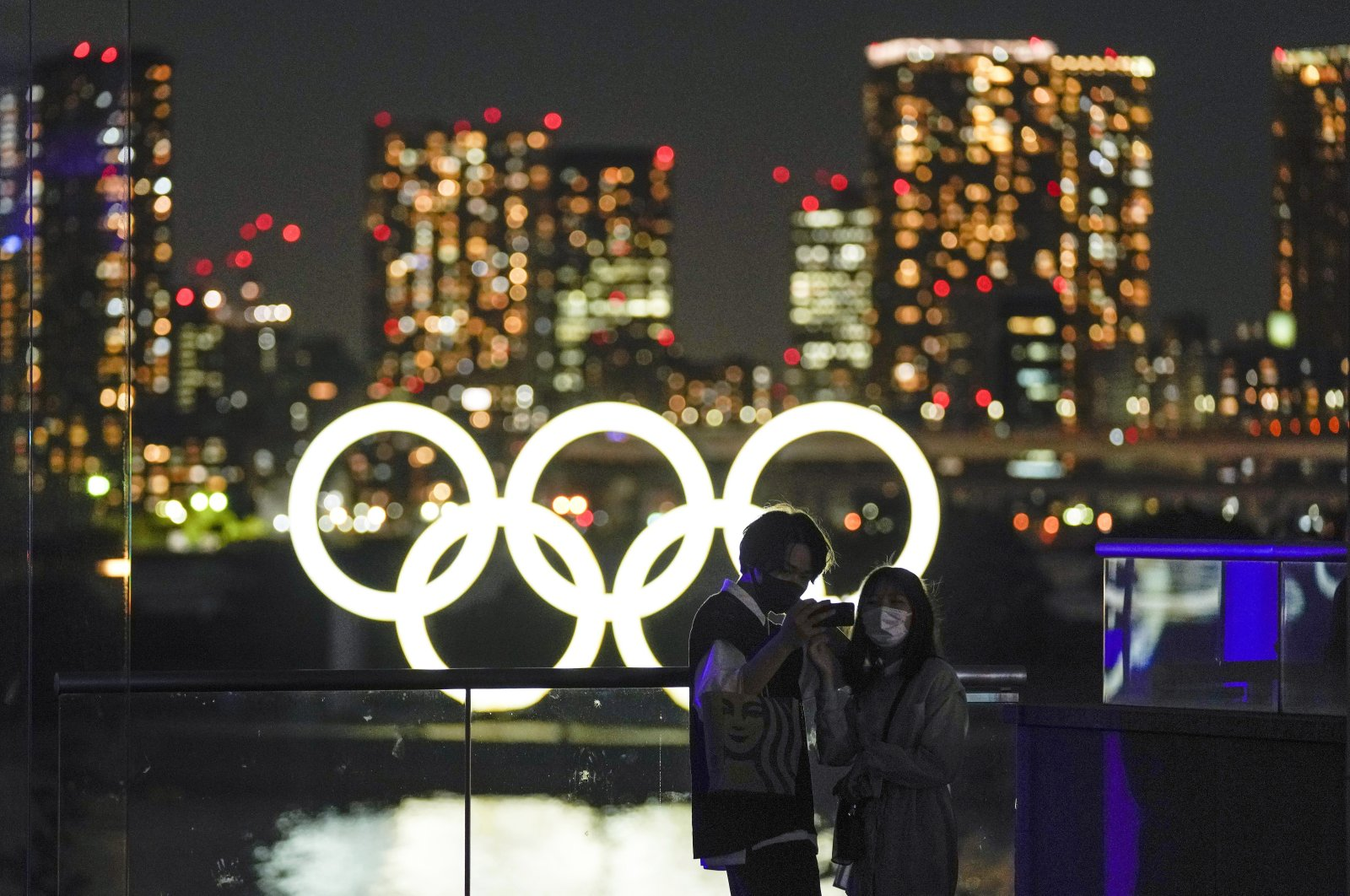A couple poses for a selfie with an Olympic Rings monument set at Odaiba Marine Park, Tokyo, Japan, May 26, 2021. (EPA Photo)