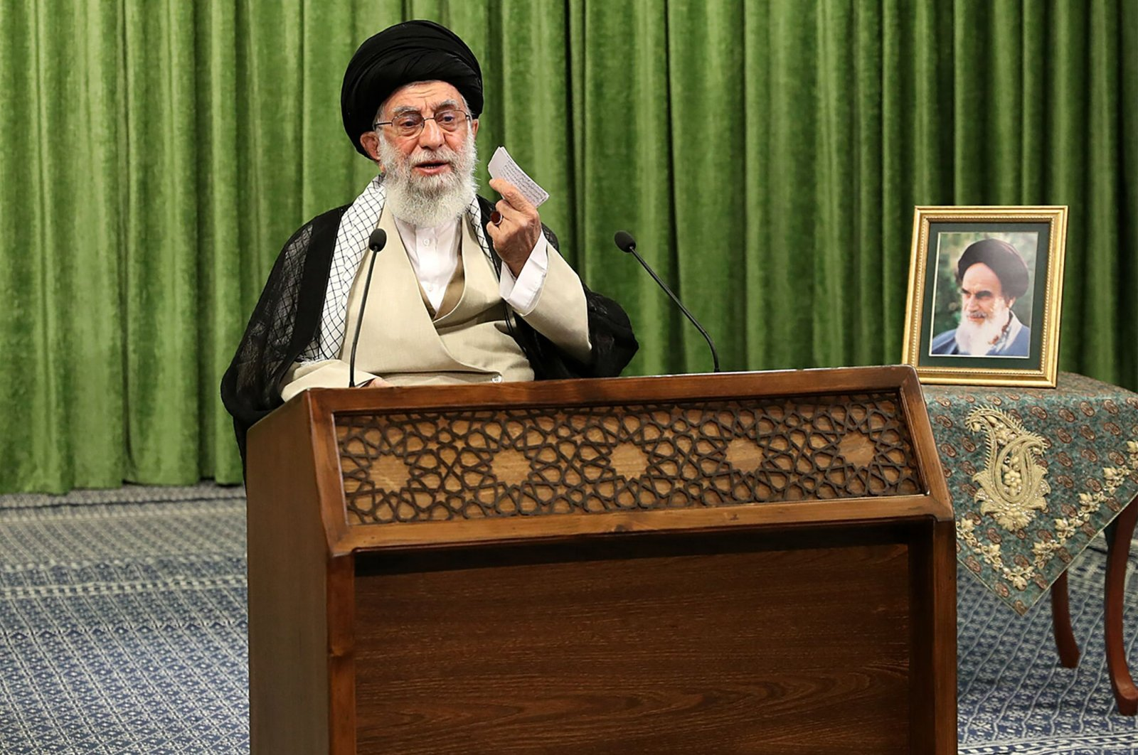 Iranian Supreme Leader Ayatollah Ali Khamenei addressing parliament members during an online meeting, with a picture of his predecessor, the late Ayatollah Ruhollah Khomeini next to him, Tehran, Iran, May 27, 2021. (Khamenei.ir handout via AFP)