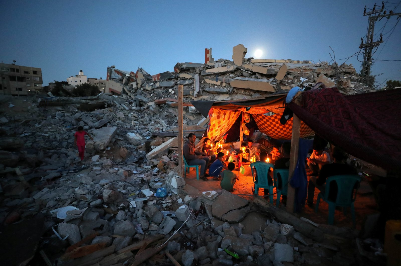 Palestinians from Zawaraa family hold candles as they sit in a makeshift tent amid the rubble of their houses, which were destroyed by Israeli air strikes during the Israeli-Palestinian fighting, Gaza, May 25, 2021. (Reuters Photo)