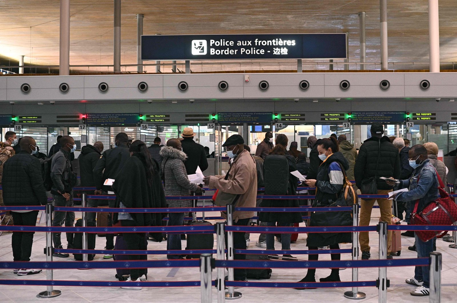 Travelers prepare their documents as they queue at the immigration desk of Roissy Charles-de-Gaulle international airport as new COVID-19 border restrictions come into effect, on Feb. 1, 2021. (AFP Photo)