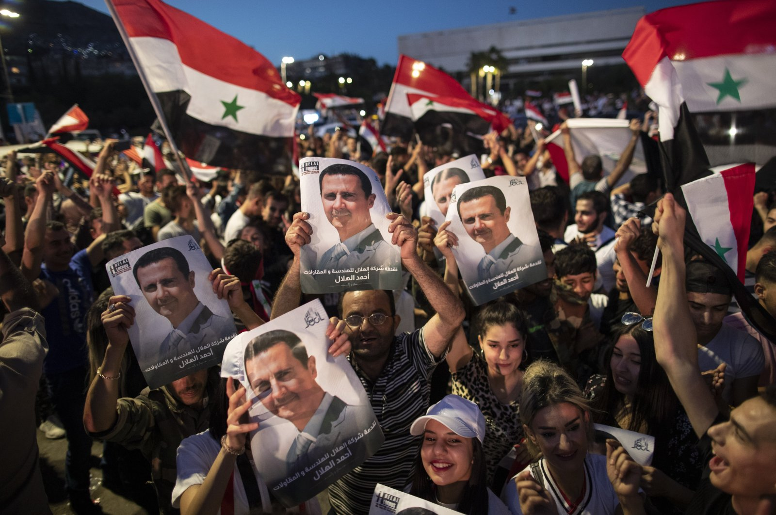 Syrian President Bashar Assad supporters hold up national flags and pictures of Assad as they celebrate at Omayyad Square, in Damascus, Syria, Thursday, May 27, 2021. (AP Photo)