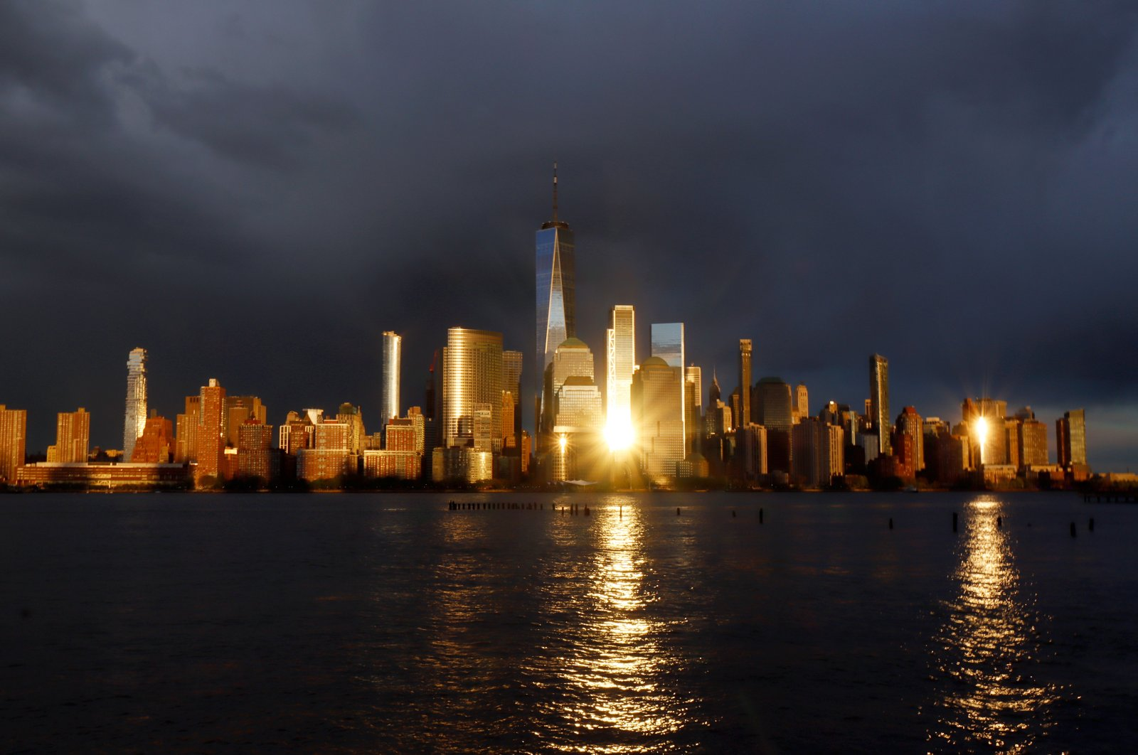 Rain clouds are seen along the skyline of lower Manhattan and the One World Trade Center as the sun sets in New York City, U.S., April 30, 2021. (Photo by Getty Images)
