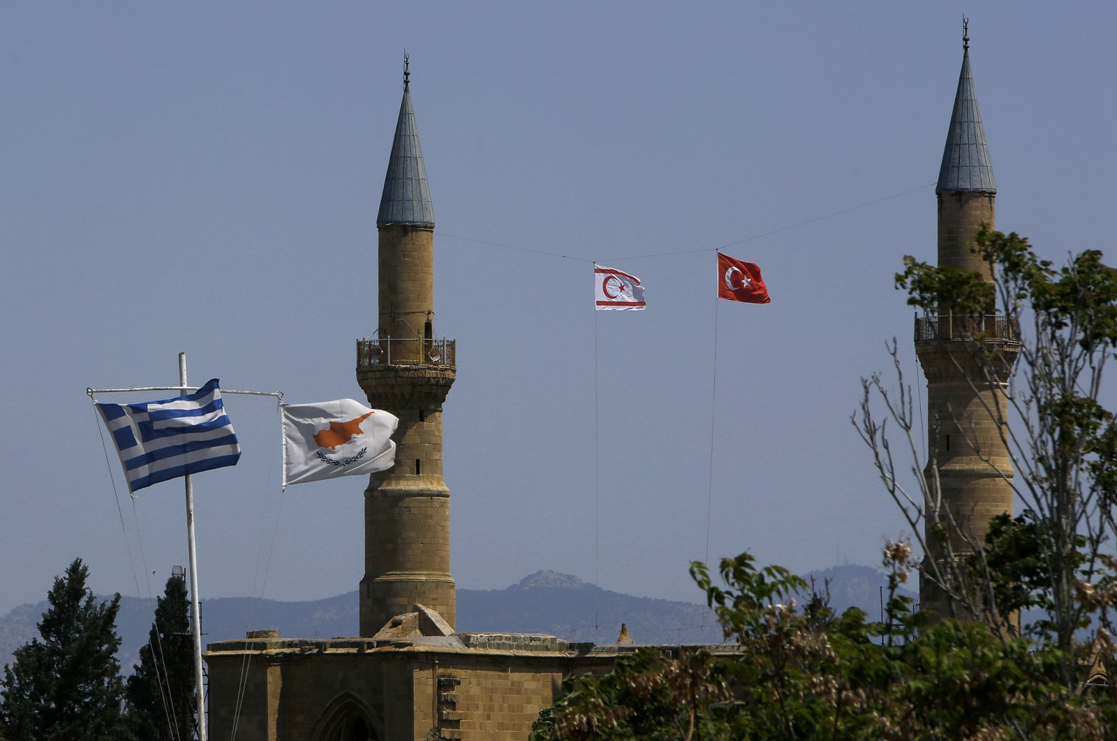 The Greek (L) and Cyprus flags (2nd L) flutter on poles in the south as in the north Turkish Cypriot area, Turkish (R) and Turkish Cypriot (2nd R) flags fly on a minaret of the Selimiye Mosque, in the divided capital Nicosia, Cyprus, April 26, 2021. (AP Photo)