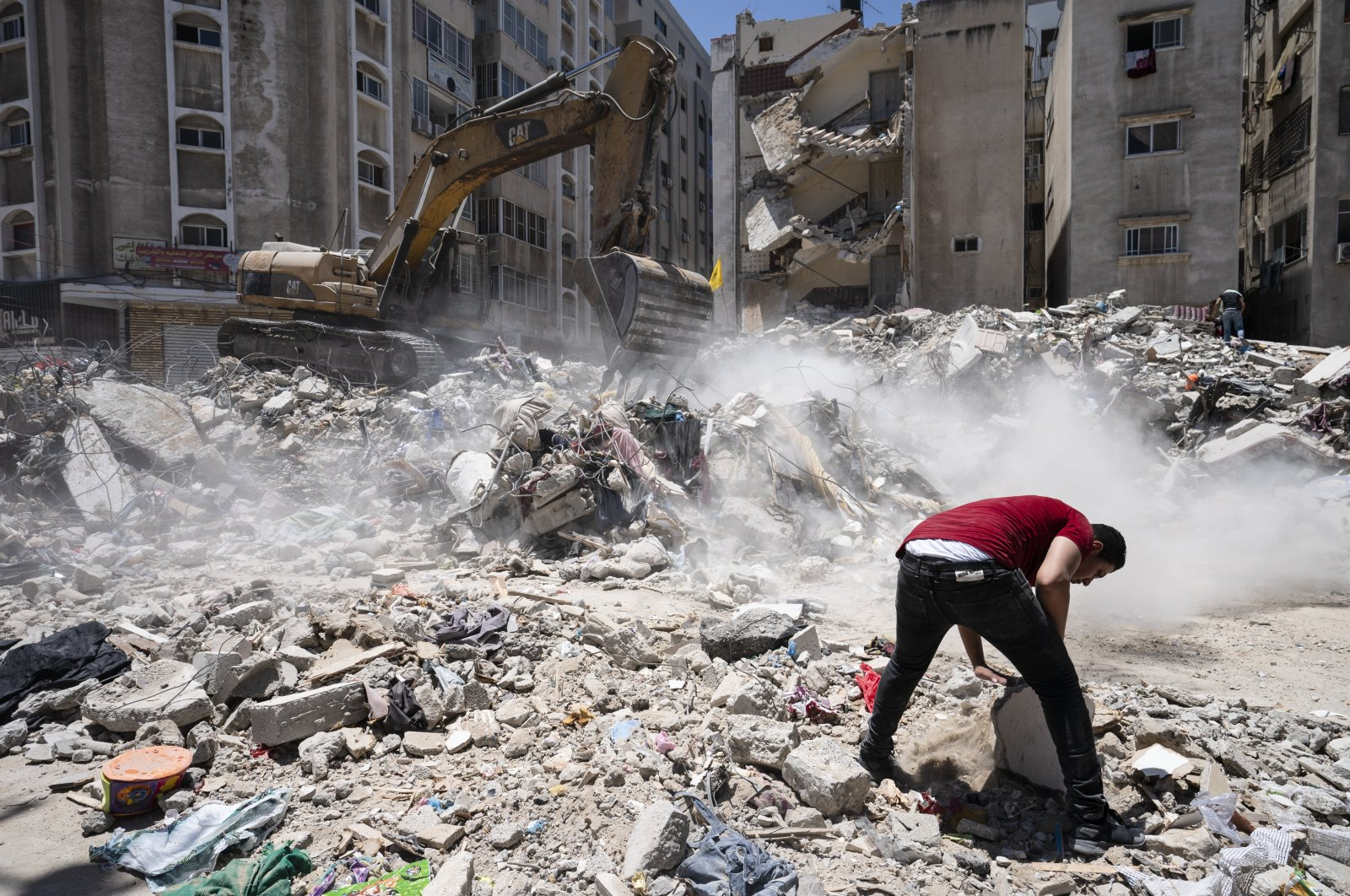 Heavy construction equipment is used to sift through the rubble to uncover valuables before it is transported away from the scene of a building destroyed in an airstrike prior to a cease-fire that halted an 11-day war between Gaza's Hamas rulers and Israel, Gaza City, May 27, 2021. (AP Photo/John Minchillo)