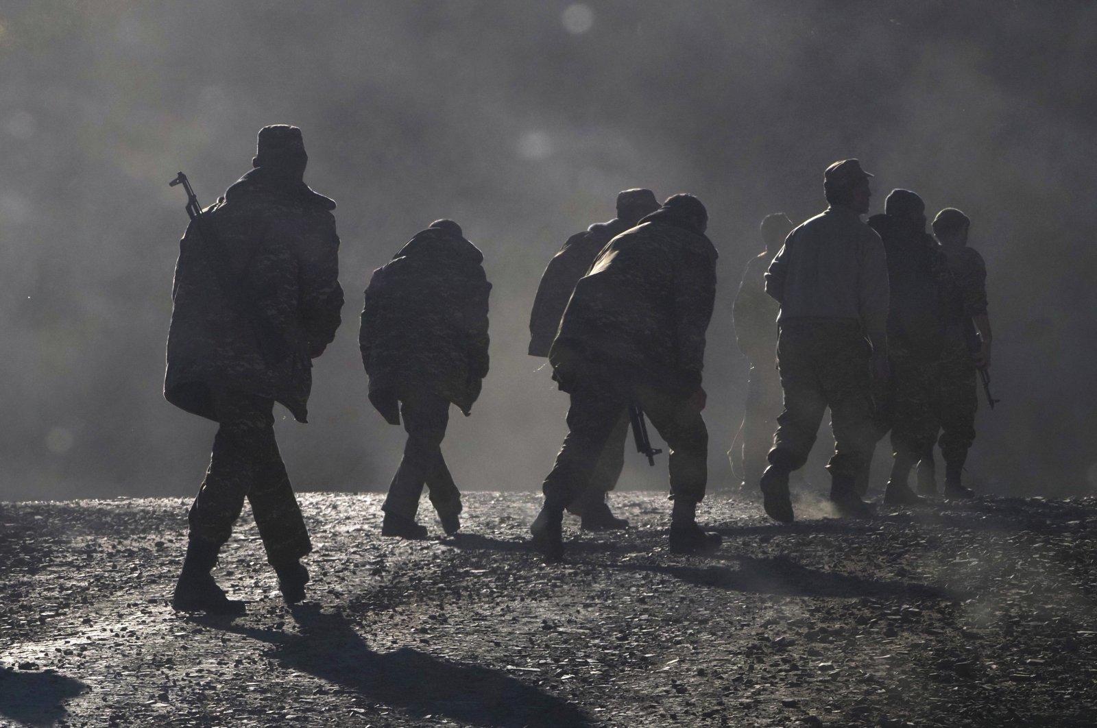 Armenian soldiers walk along the road near the border between Nagorno-Karabakh and Armenia, Sunday, Nov. 8, 2020. (AP Photo)