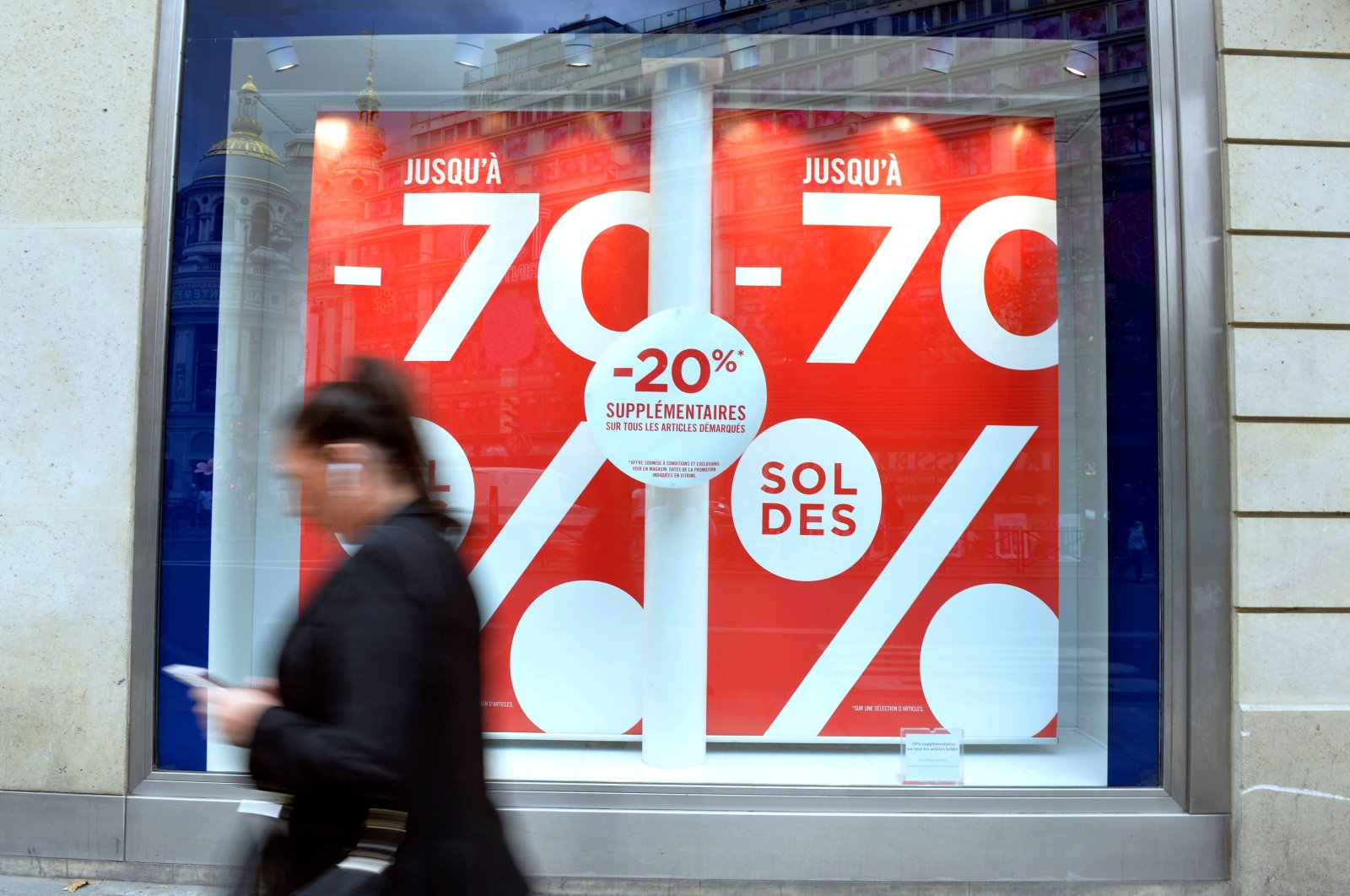 A woman walks past a storefront advertising last-day-of-summer sales, in Paris, France, Aug. 4, 2015. (AFP Photo)