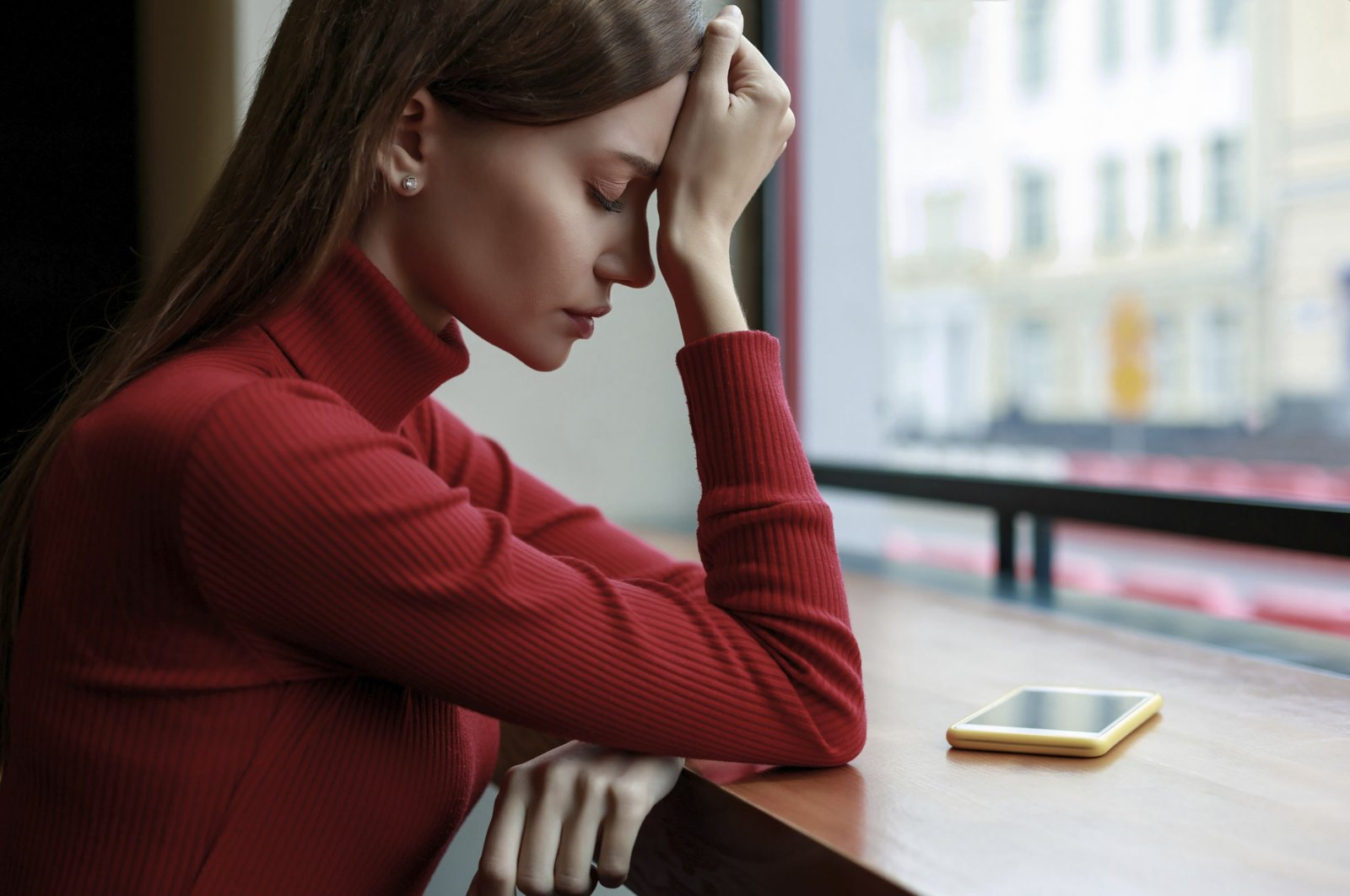 A young woman with anxiety struggles in a cafe. (Getty Images)