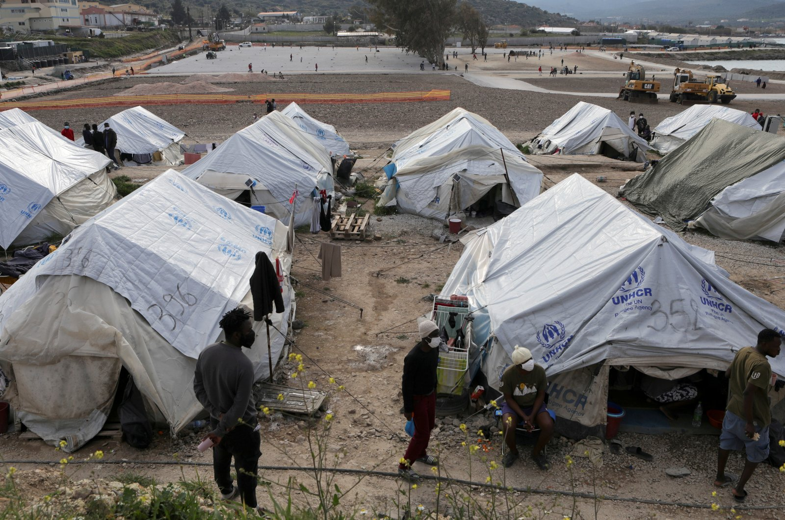 Refugees and migrants stand next to tents in the Mavrovouni camp on the island of Lesbos, Greece, March 29, 2021. (Reuters Photo)