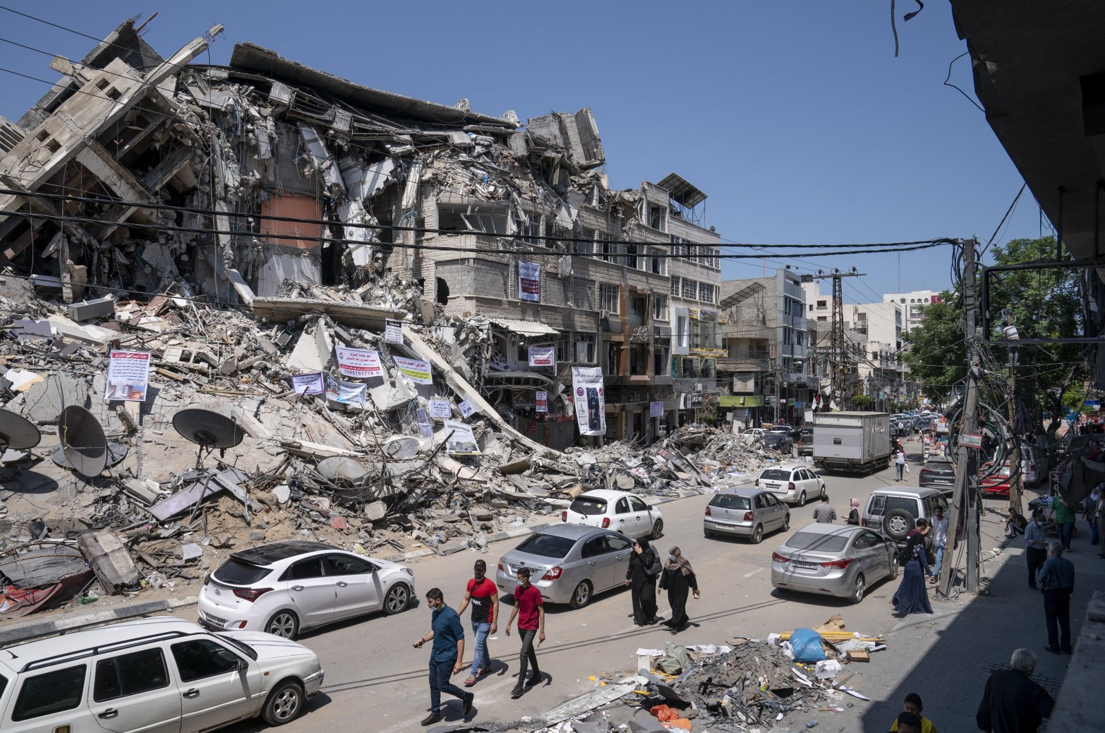 Motorists and pedestrians move past a building destroyed by an airstrike prior to a cease-fire that halted the 11-day war between Gaza's Hamas rulers and Israel in Gaza City, the Gaza Strip, May 25, 2021. (AP Photo)